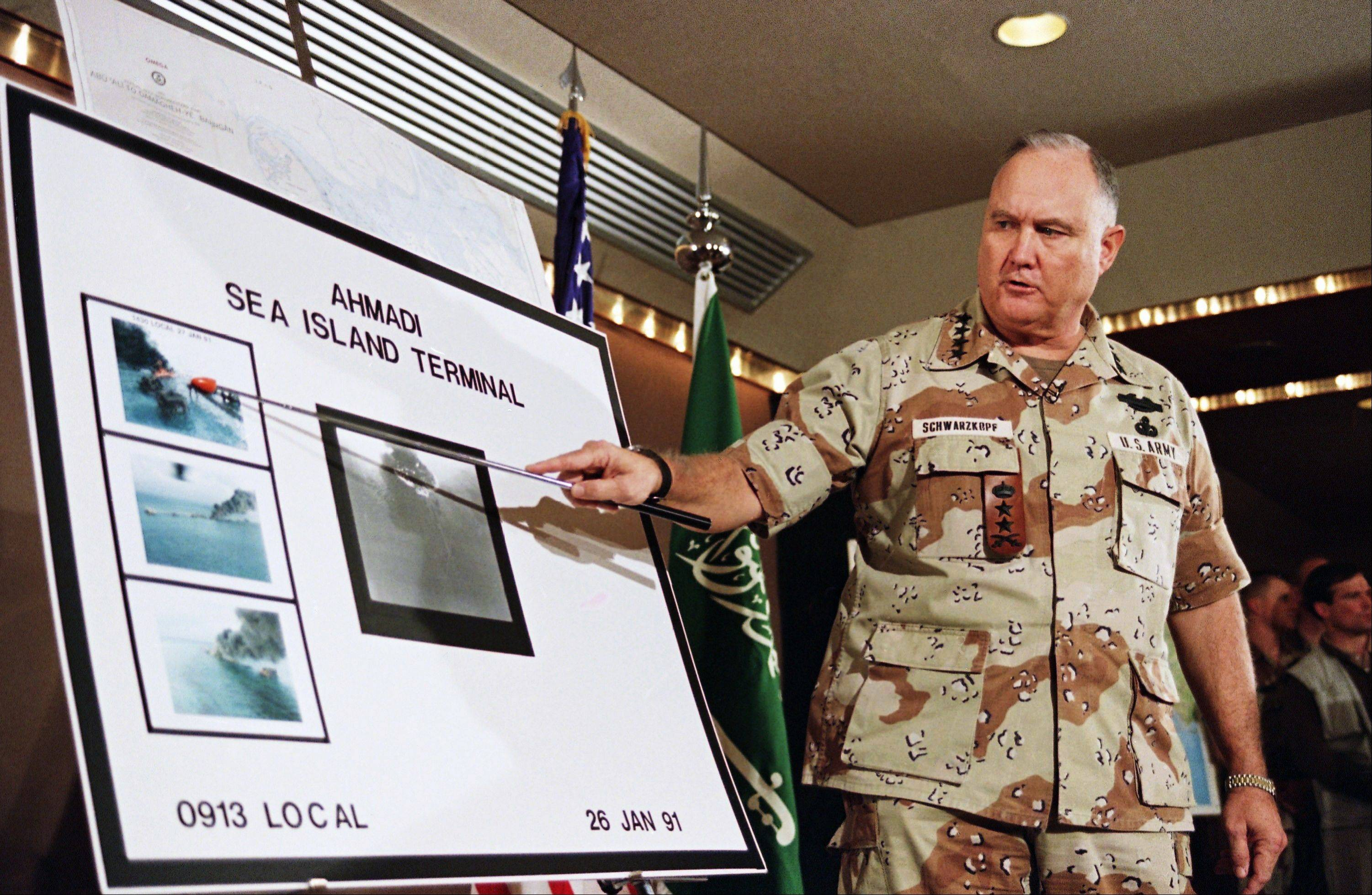 U.S. Army Gen. Norman Schwarzkopf points to row of photos of Kuwait's Ahmadi Sea Island Terminal on fire after a U.S. attack on the facility.