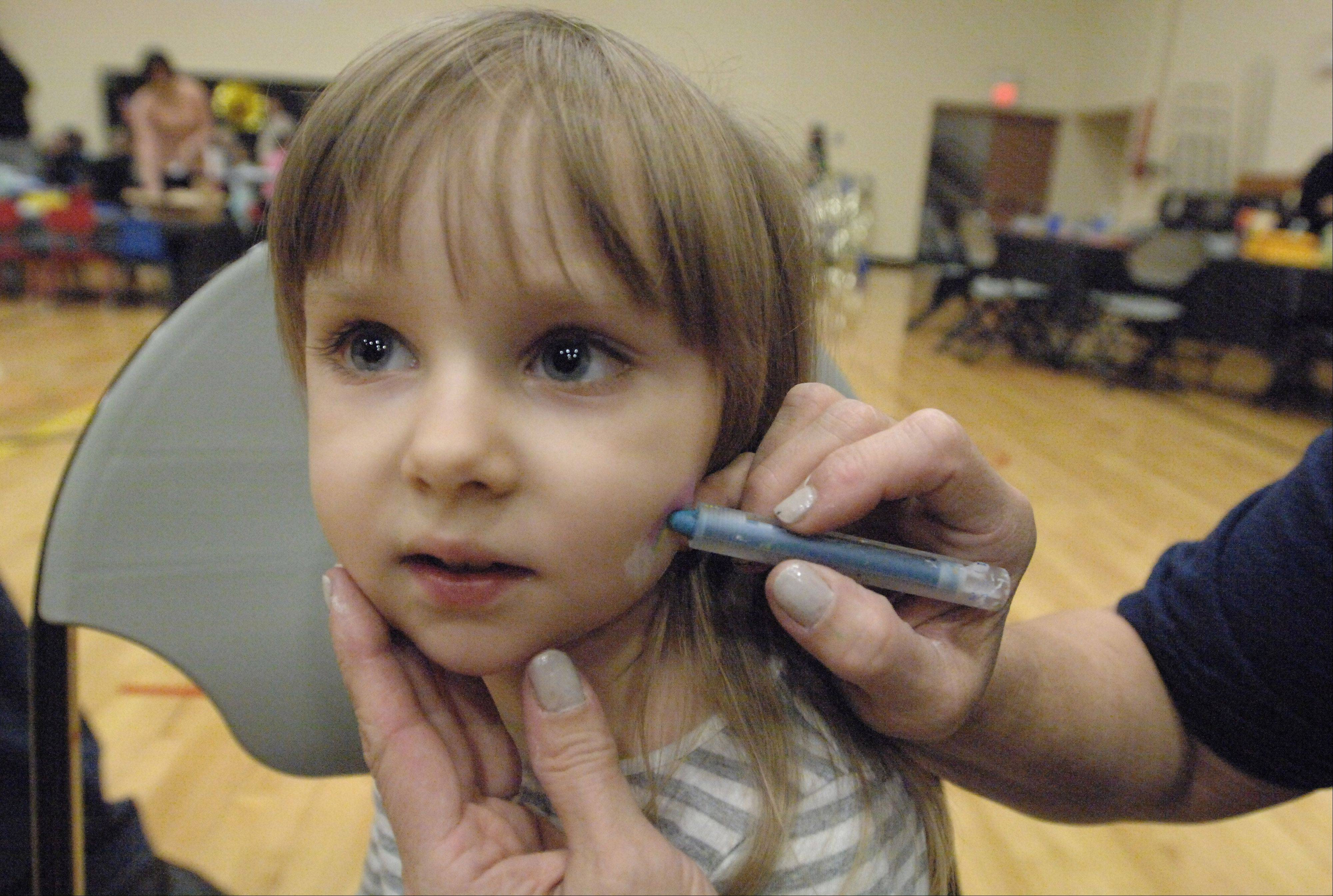 Evelyn Mosena, 3, of Carol Stream, gets her face painted Saturday at the Carol Stream Park District's Teenie Weenie New Year's Eve Ball.