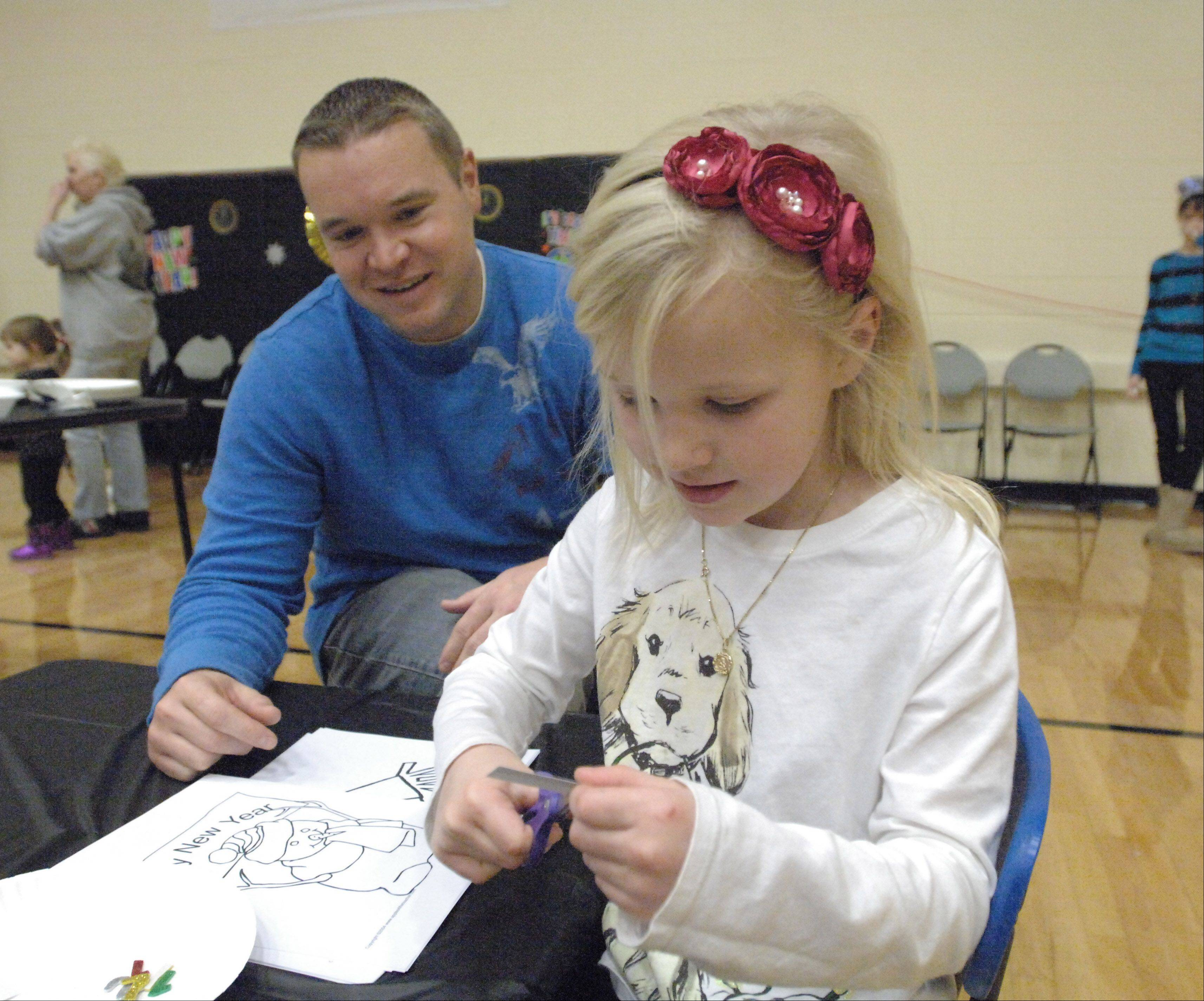 Brian Machesky of Crystal Lake and his five-year-old daughter, Abby, make a clock craft Saturday during the Carol Stream Park District's Teenie Weenie New Year's Eve Ball.