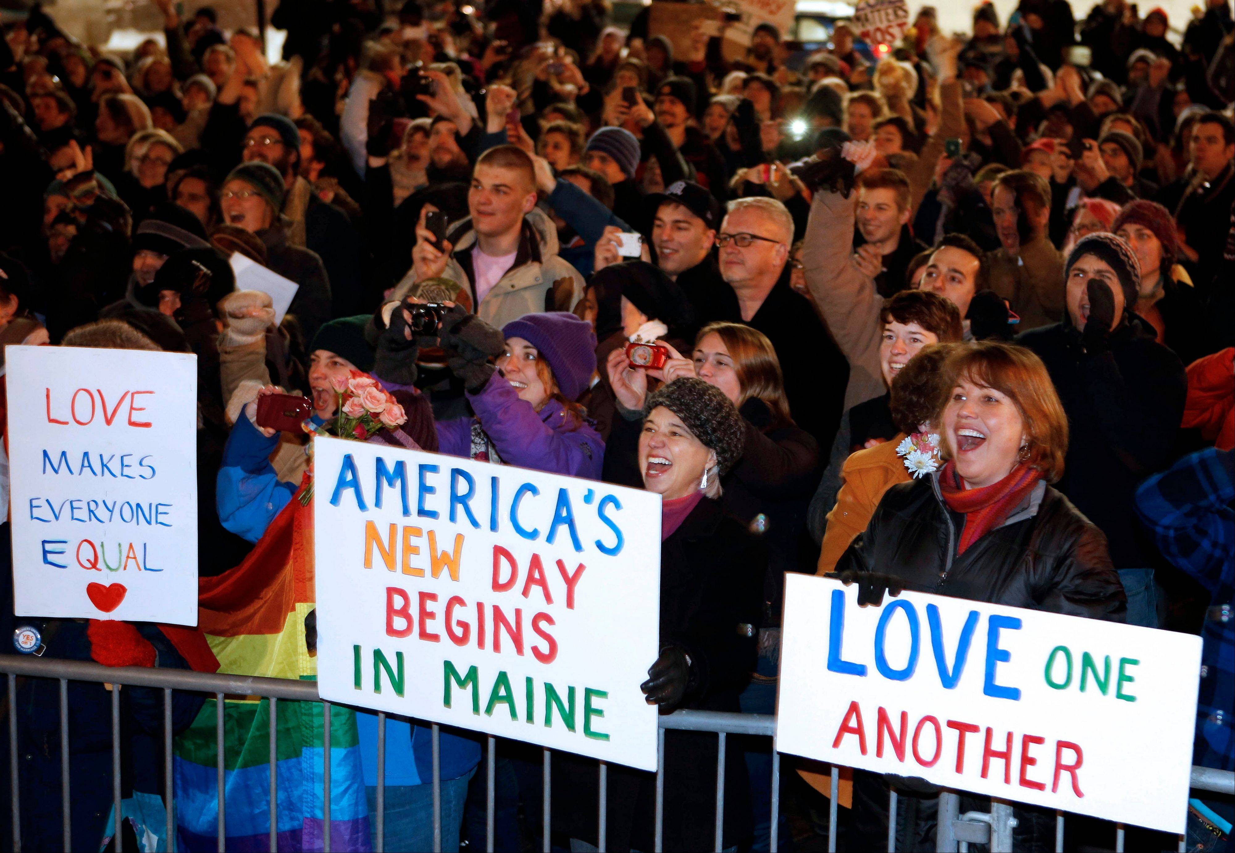 A crowd cheers at 12:30 a.m. Saturday, Dec. 29, as the first same-sex couple to be legally married in Maine departs City Hall in Portland, Maine.