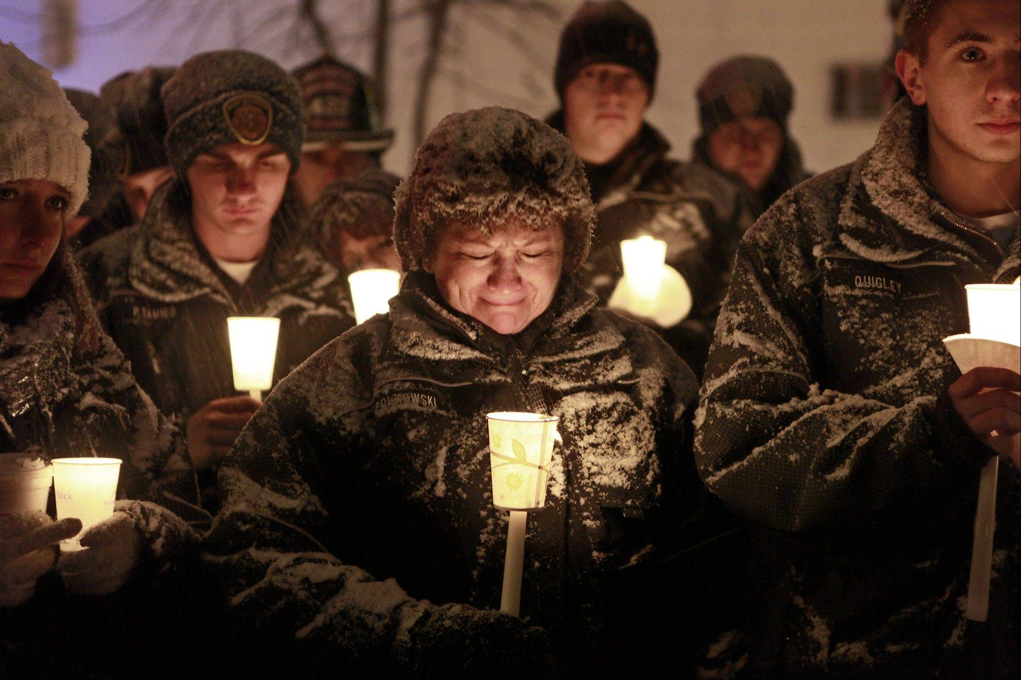In this Wednesday, Dec. 26, West Webster firefighter Vicki Polkowski, center, sheds tears, in Webster, N.Y., as the Fireman's Prayer is read aloud at a candlelight vigil held in honor of the firefighters that were injured and killed on Christmas Eve.
