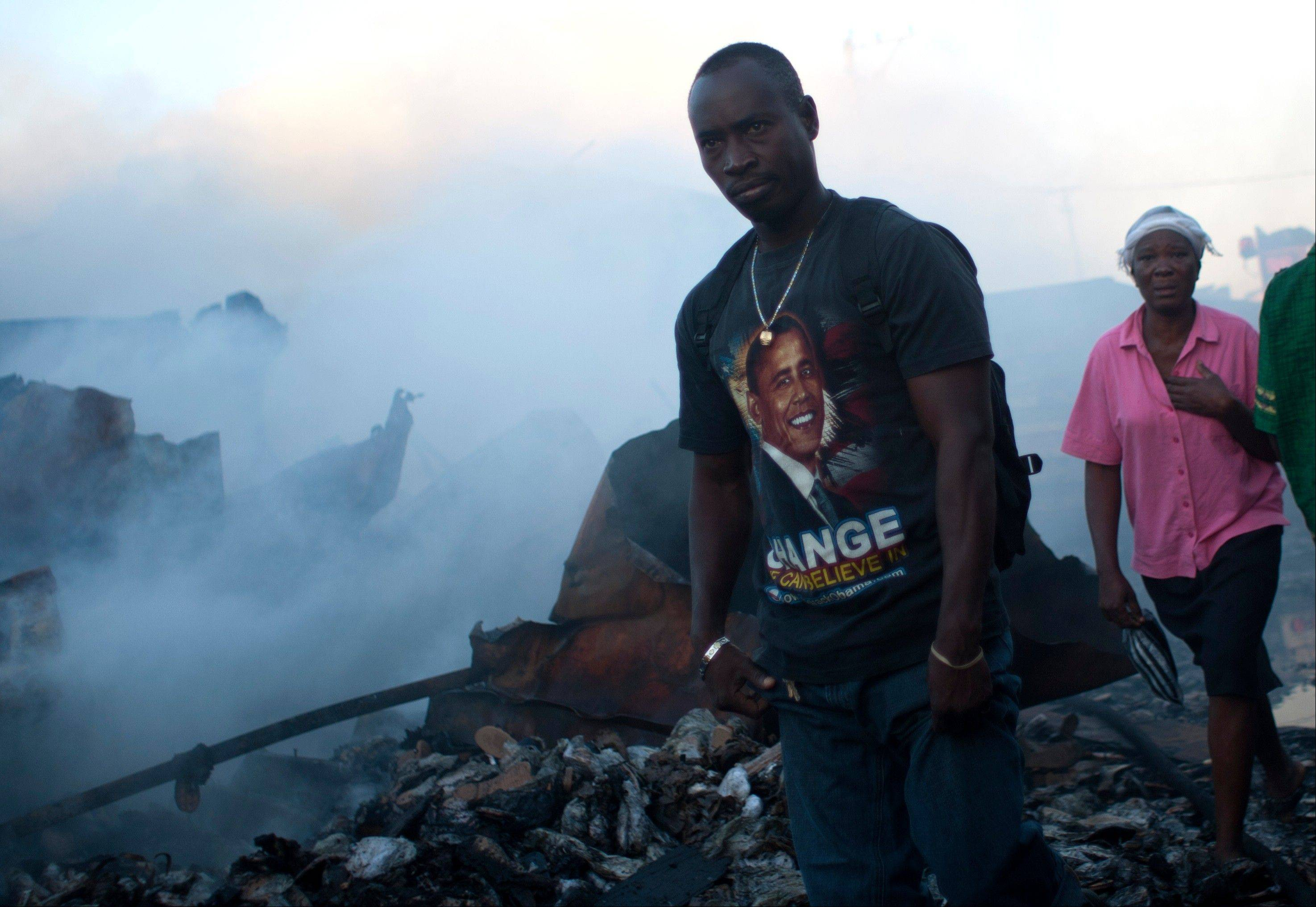 People walk by the remains of a market burned in an overnight fire in the Haitian capital's Market District in Port-au-Prince, Haiti, Saturday, Dec. 29. The market is one of several that have burned over the past year.