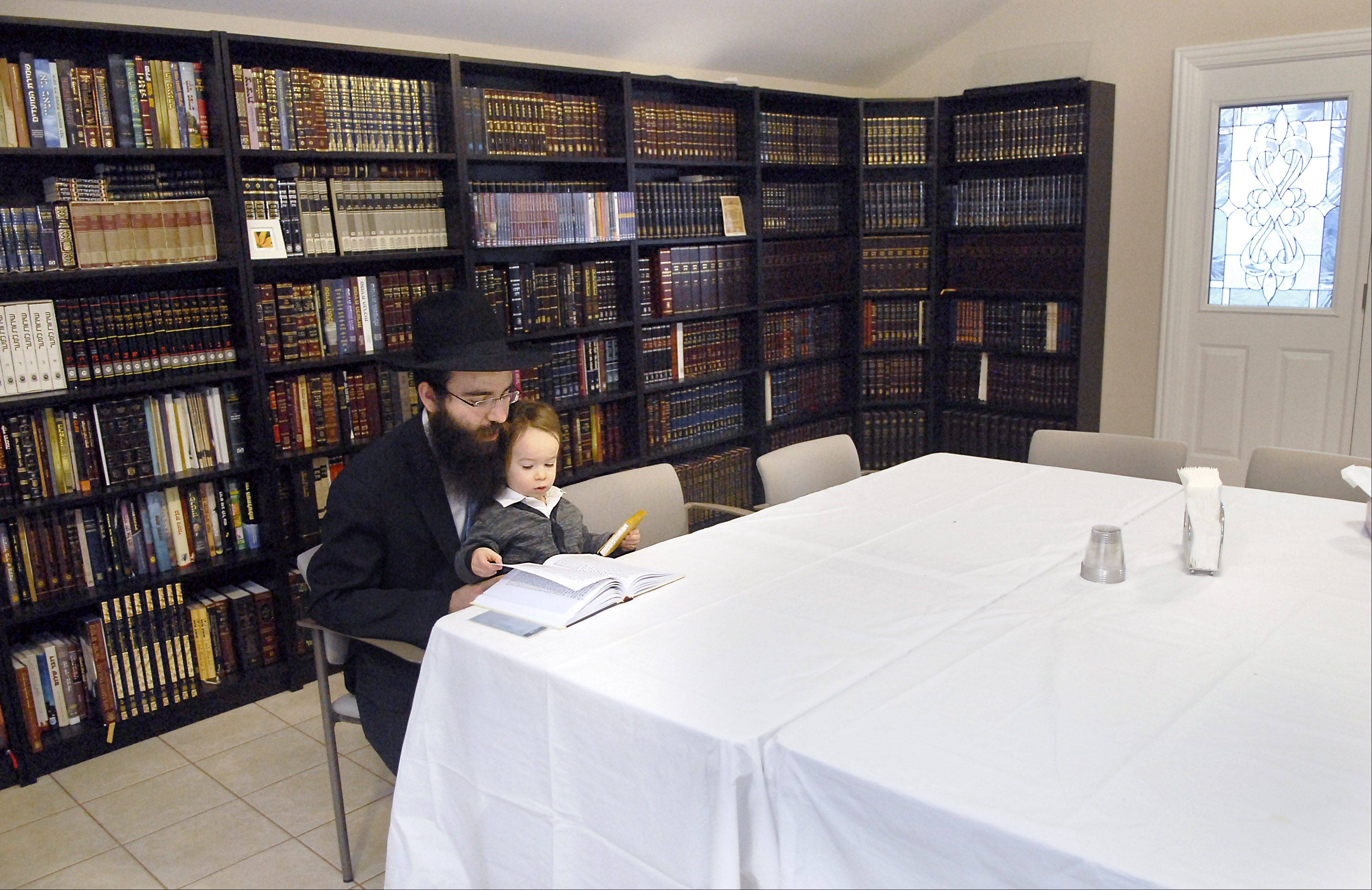 Rabbi Mendel Shemtov and his son, Levi, 21 months, read in the room where classes are offered for adults and children at the Chabad of Elgin & Hoffman Estates.