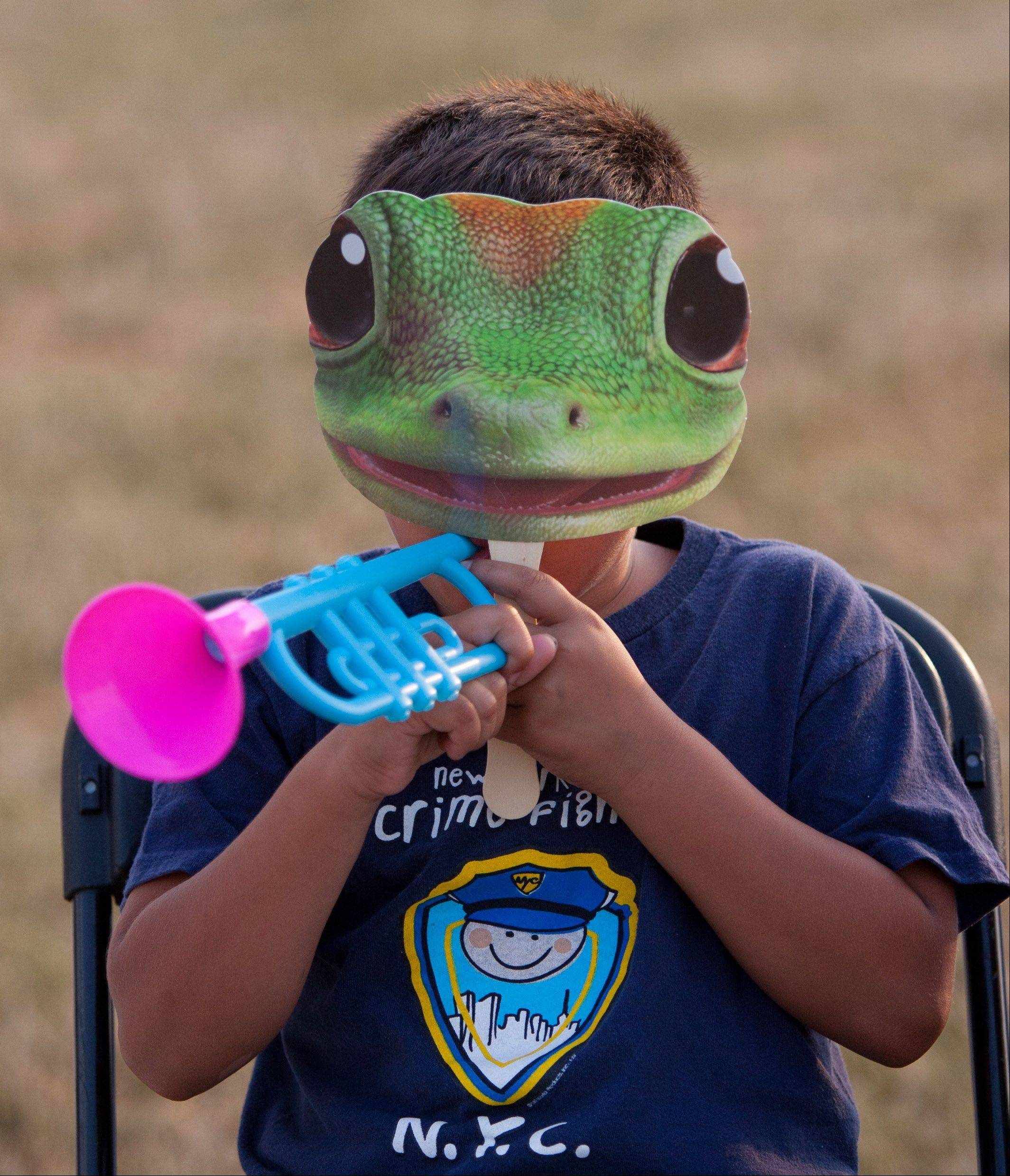 Julio Moreno, 5, of West Chicago waits to hear music as he relaxes behind the Geico Gecko trademark, during the second day of Railroad Days in West Chicago.