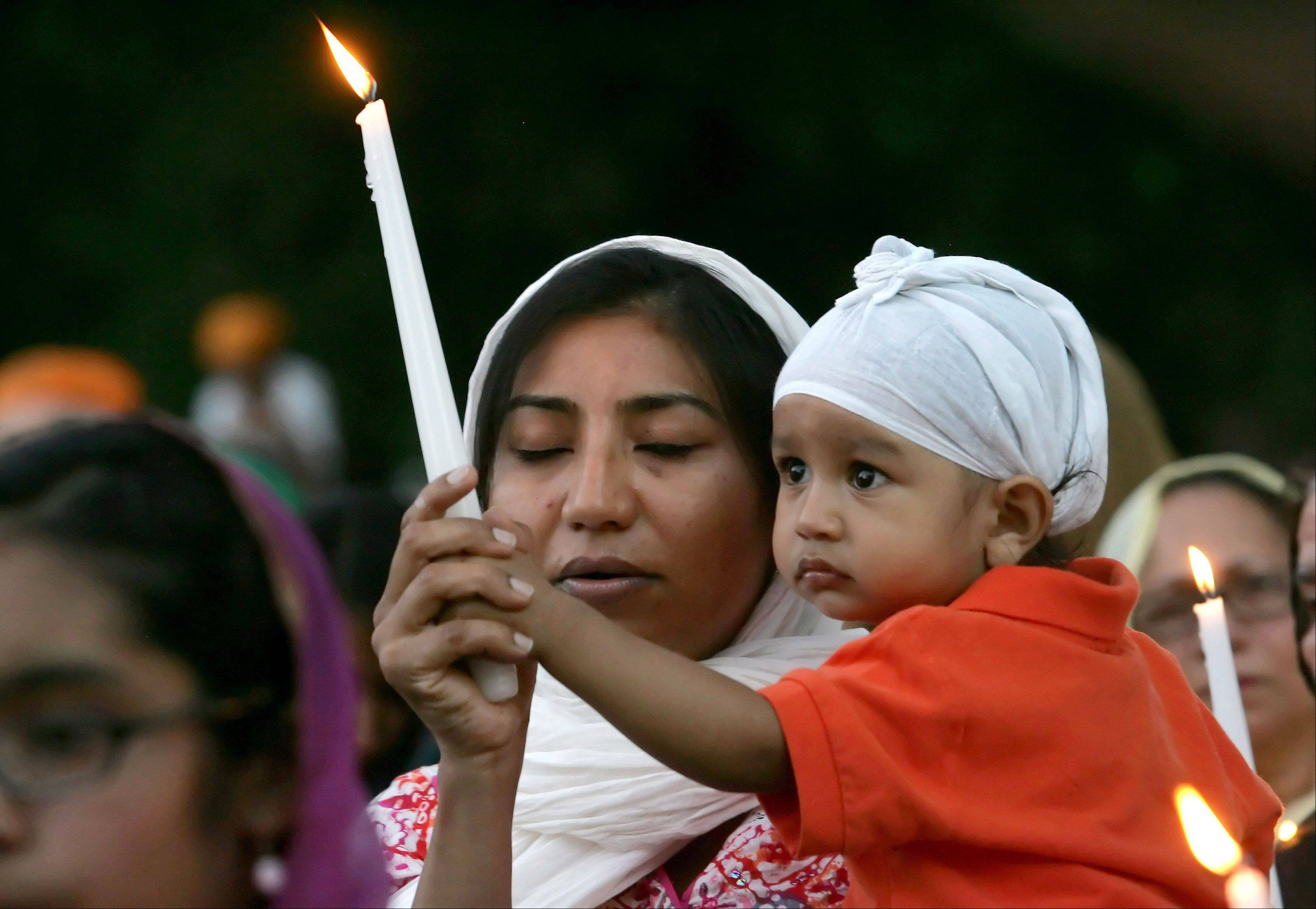 Kawal Preet and her son Prabhnek, 15 months old, visiting from San Franciso, take part in the candlelight vigil at Illinois Sikh Communty Center in Wheaton in the wake of shootings at a Wisconsin Sikh temple.