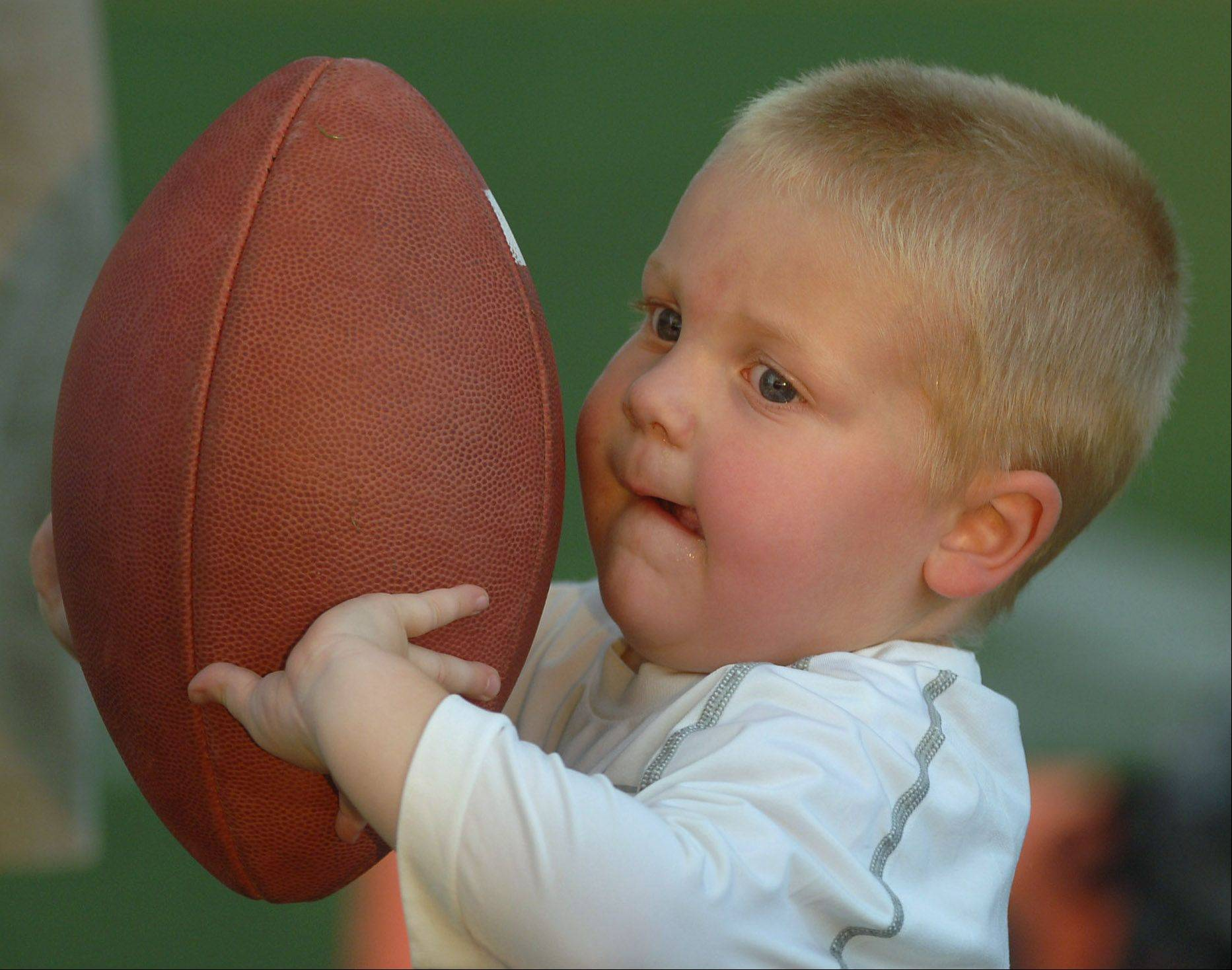 Two-year-old Quinten Boekholder tries out his football handling skills Friday night during a Lake Zurich home game against Fremd. Quinten's dad, Nate Boekholder, is an assistant varsity football coach for the Lake Zurich Bears.