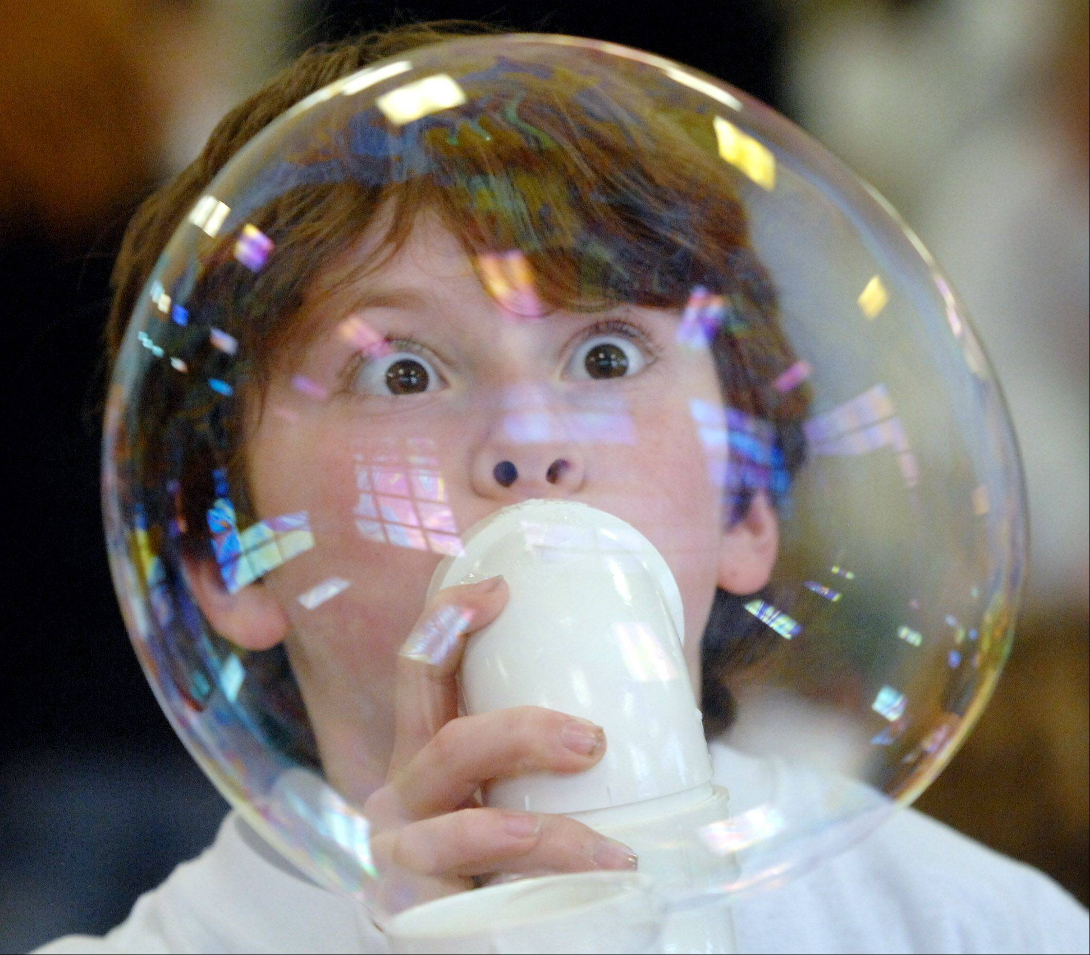 Fremont third grade student Kyle Appelhans gets a close look at a large soap bubble he's blowing during District 79's STEAM Teams program at the Mundelein school. The after-school program explores the connections between science, technology, engineering, art and math (STEAM).