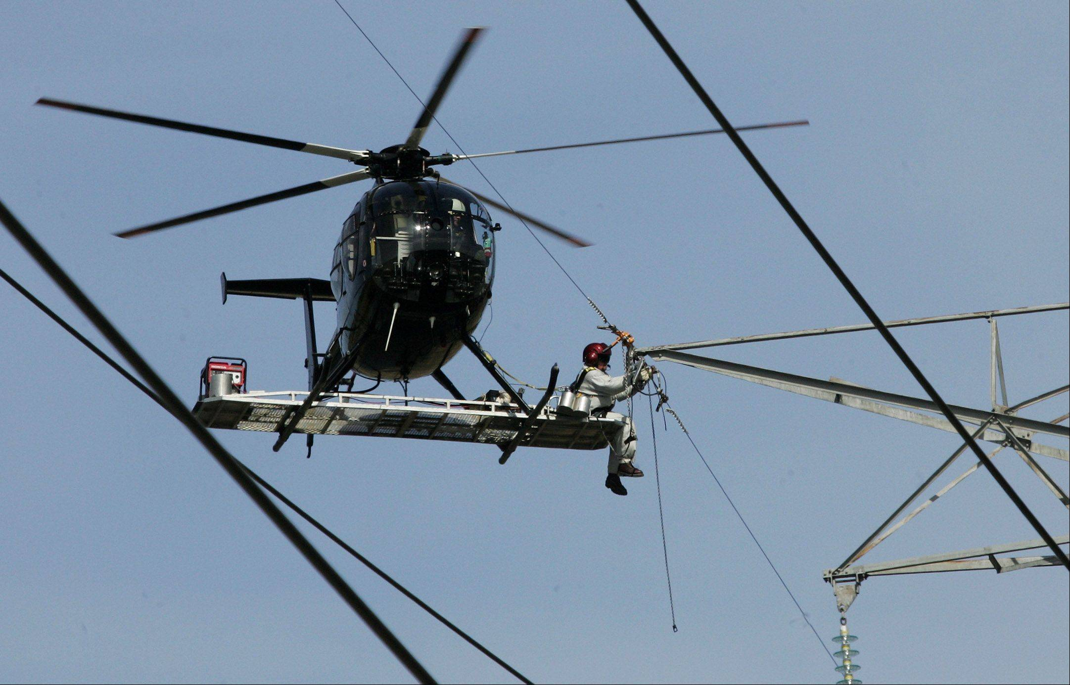 Personnel from ComEd use a helicopter and a maintenance linesman to work on high-tension power voltage lines along Milwaukee Avenue north of Route 137 in Libertyville. Technicians wear electric-field-resistant suits and because the helicopters are not touching the ground, this doesn't cause a high-voltage arc, and the work can be done on live wires.