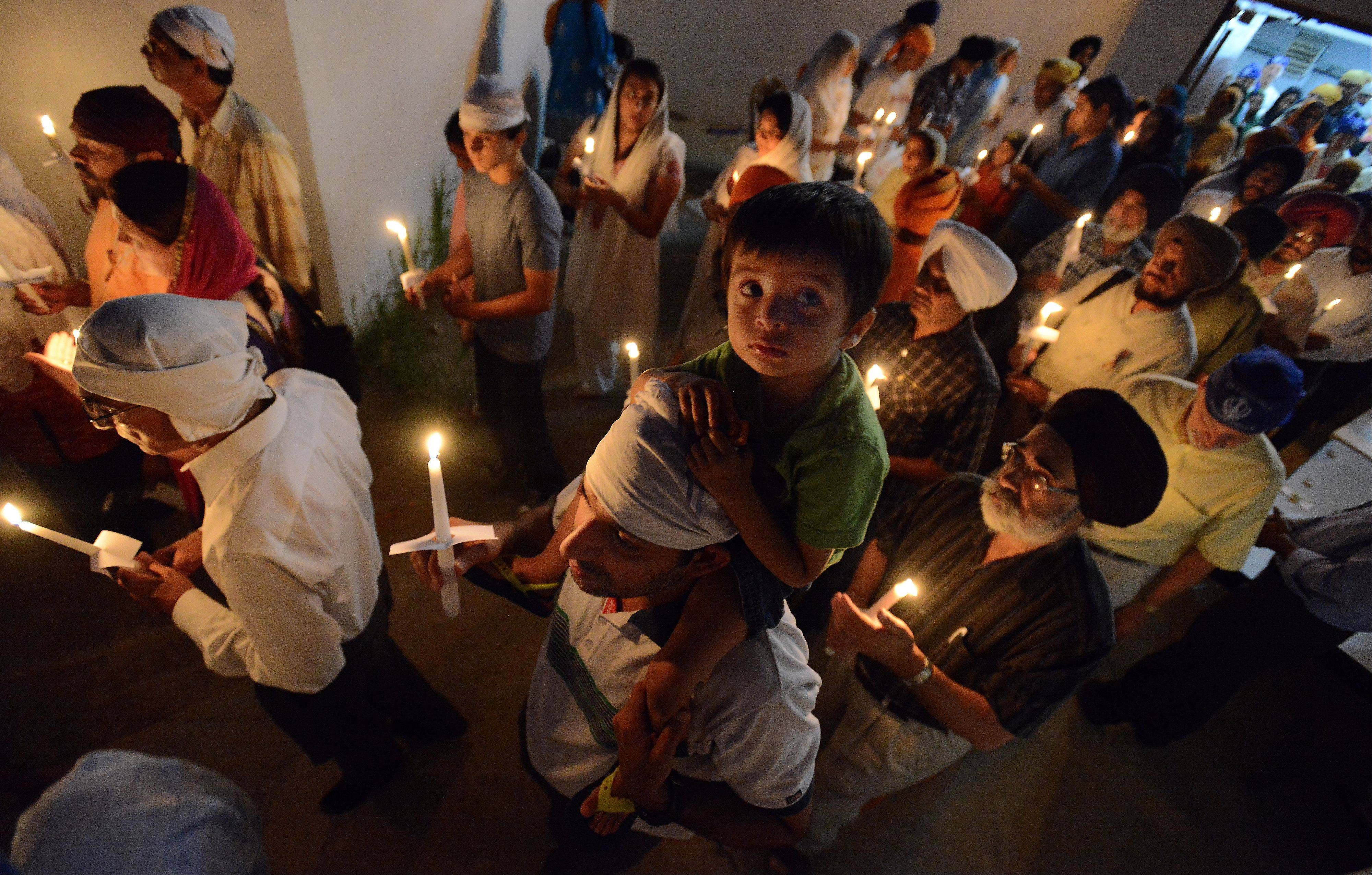 Sikh women and men hold candles for the vigil that was held in Palatine at the Sikh Religious Society temple to honor and remember those who were killed in a Wisconsin Sikh temple shooting.