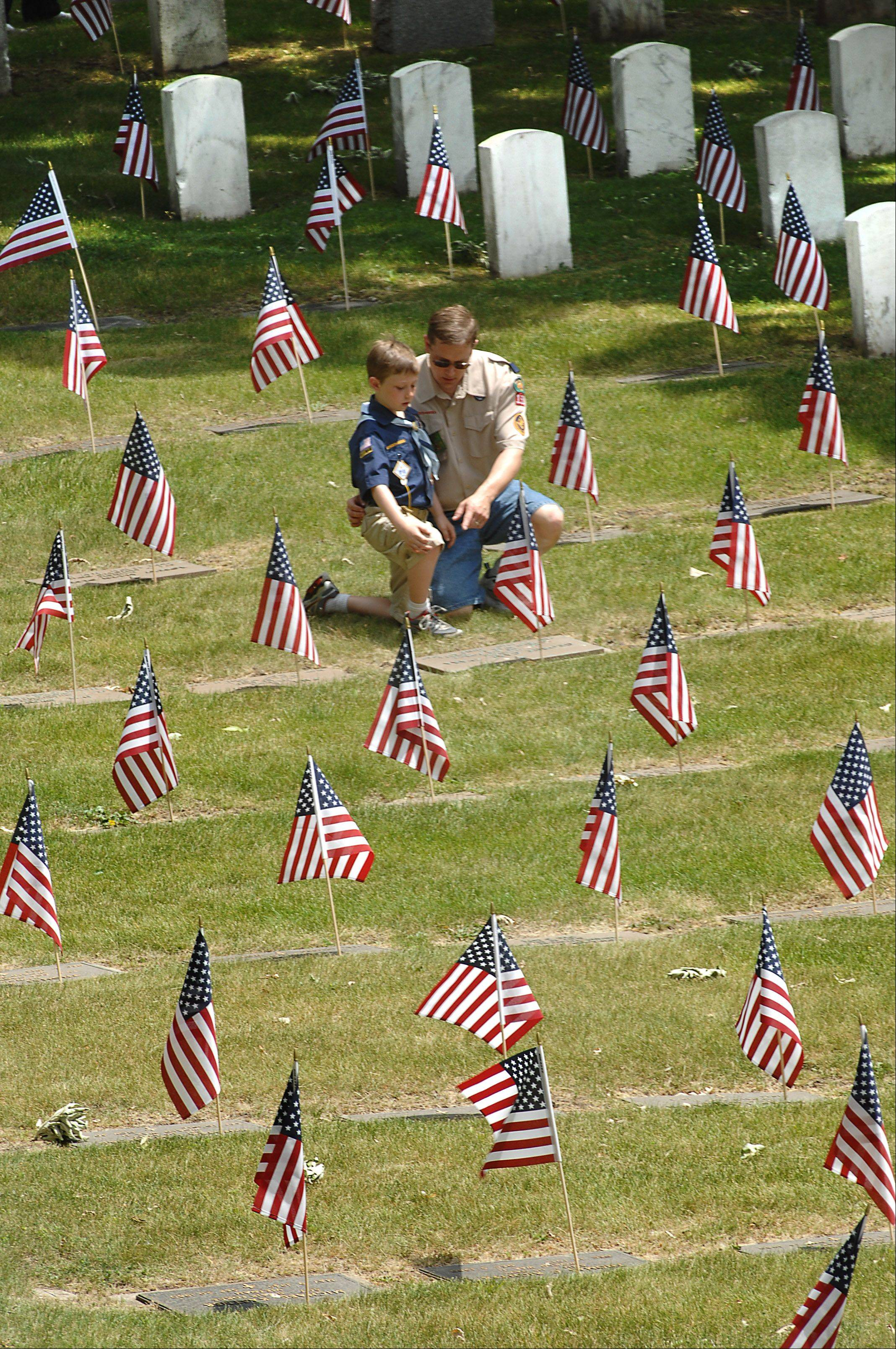 Cub Scout Collin Hagen, 8, and his father Jerry of South Elgin spend time with soldiers graves in the Bluff City Cemetery following the Memorial Day ceremony in Elgin.