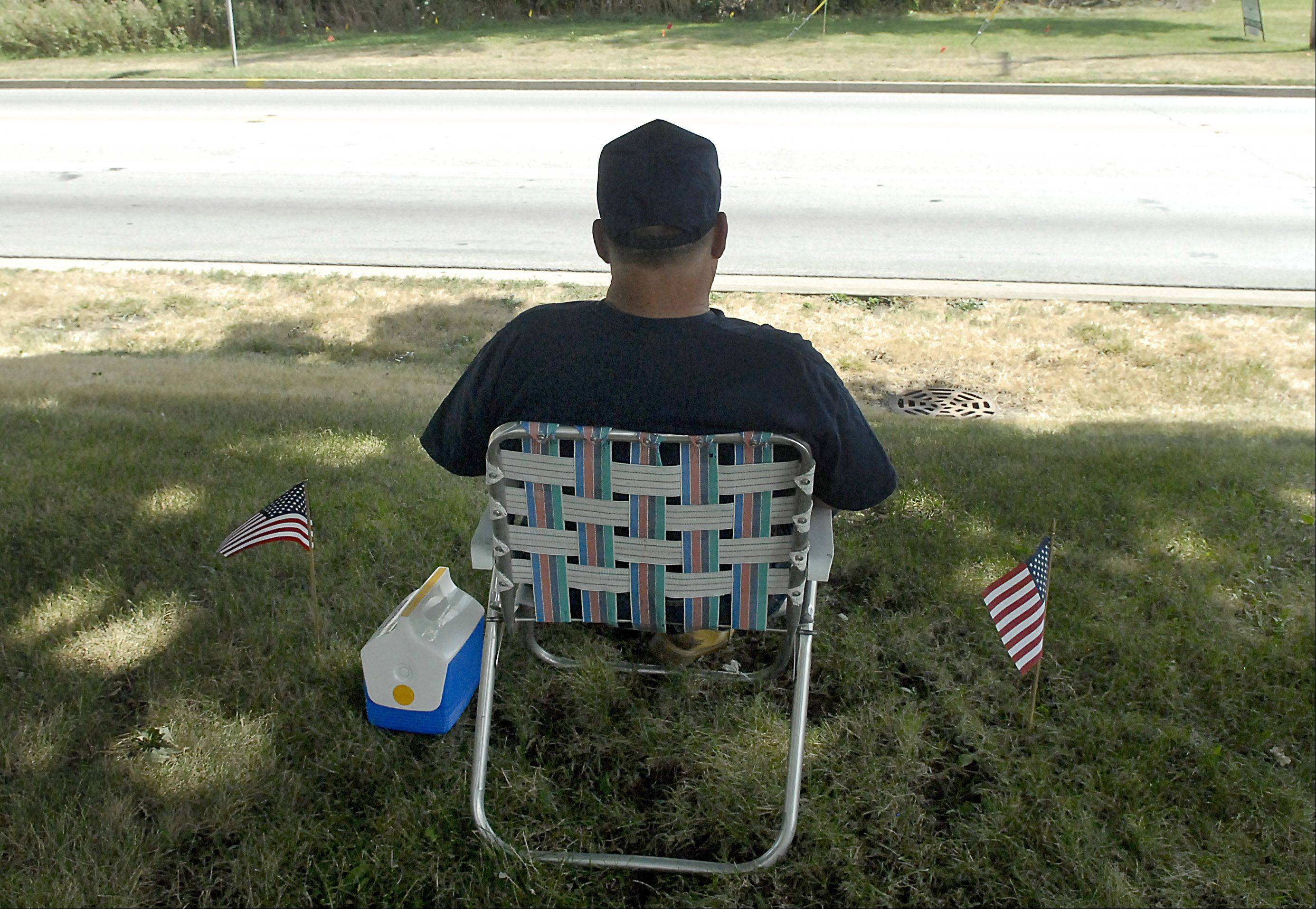 "Bill Keith of Crystal Lake waits for the motorcade escorting the hearse of U.S. Navy Petty Officer John Larimer to drive down East Terra Cotta Avenue in July. Keith, a US Navy Vietnam veteran who served on the USS Cree, ATF-84 (Auxilary Tug Fleet), knew Larimer as a boy scout in Troop 168. Keith, an Assistant Scout Master at that time, remembered Larimer as, ""Just a good kid, full of life."""