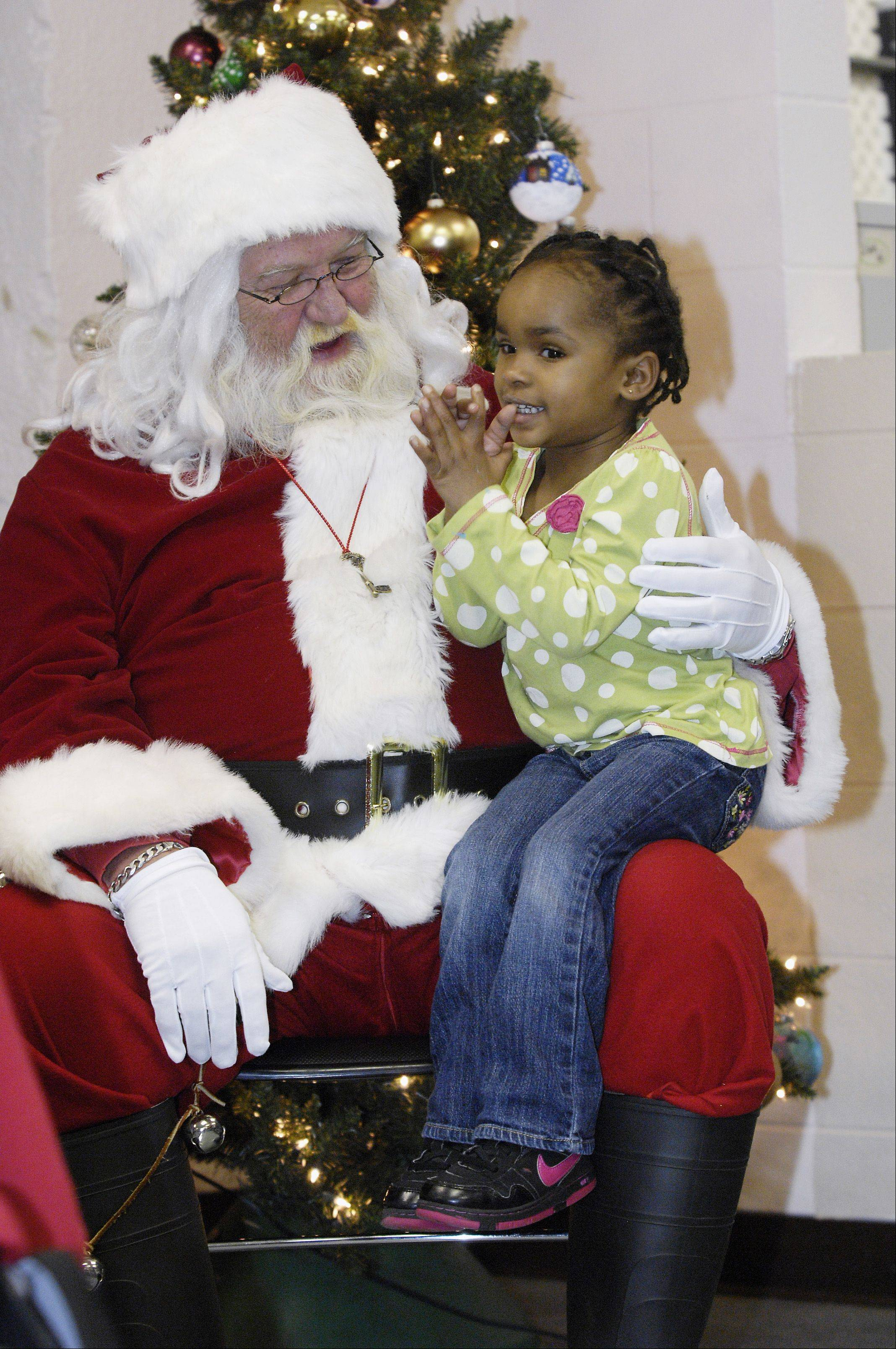 Makayla Mudd, 3, sits on Santa's lap to tell him her Christmas wishes.