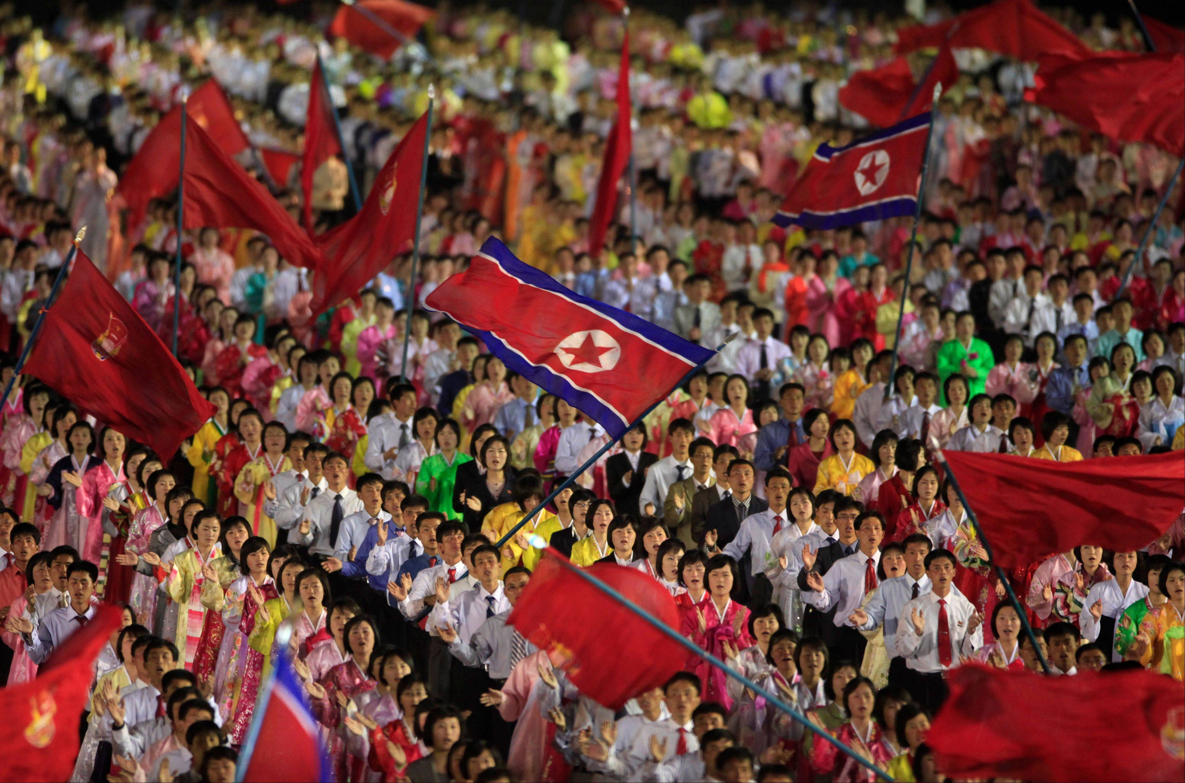 Students wave the national flags at an evening dancing party and performance at Kim Il Sung Square to commemorate late President Kim Il Sung's 100th birthday in Pyongyang, North Korea.
