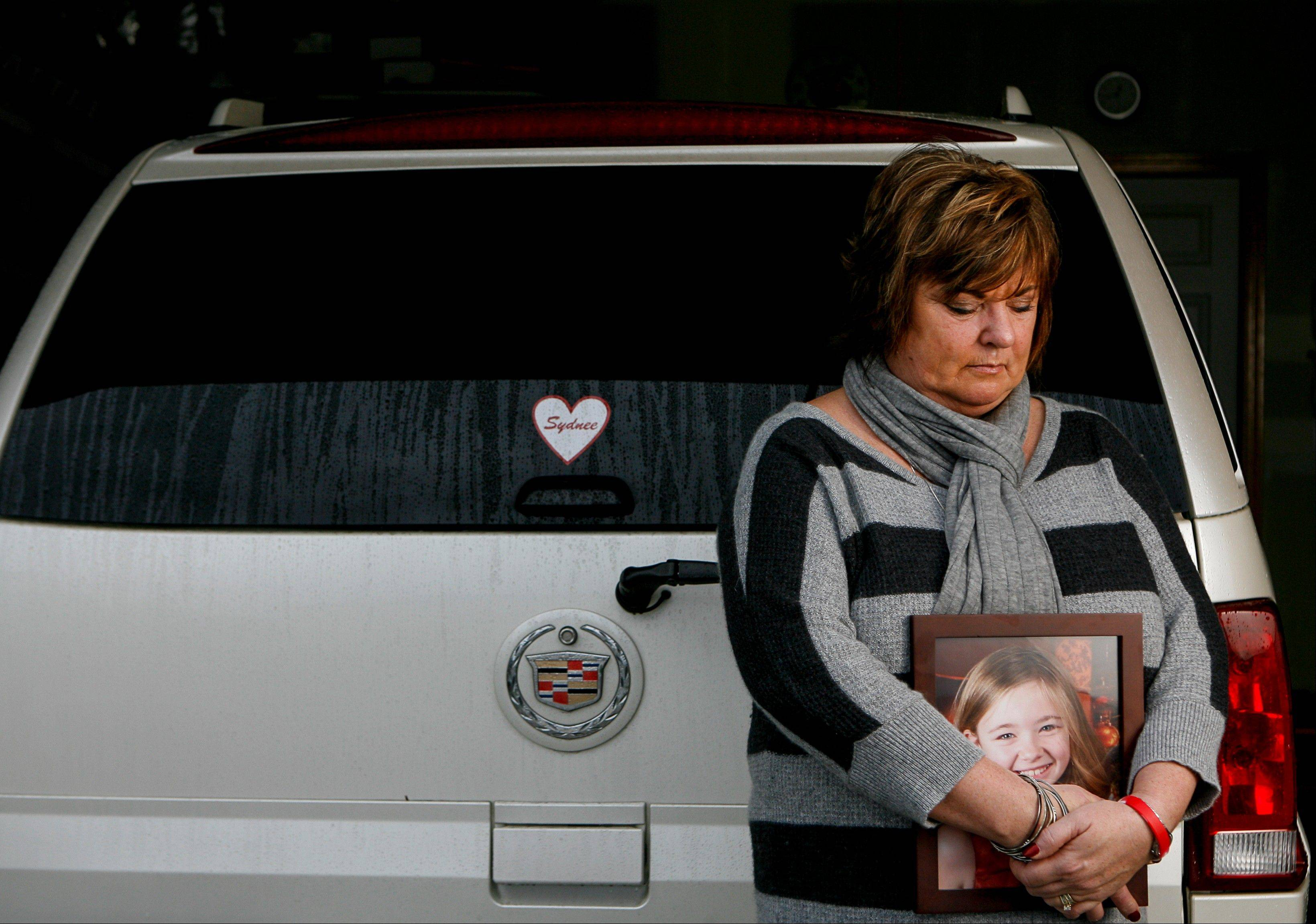 Judy Neiman holds a photo of her daughter, Sydnee, in front of her 2006 Cadillac Escalade at her home in West Richland, Wash. Sydnee died in late 2011 after Neiman accidentally backed over her with the SUV. Although there is a law in place that calls for new manufacturing requirements to improve the visibility behind passenger vehicles, the standards have yet to be mandated because of delays by the U.S. Department of Transportation.
