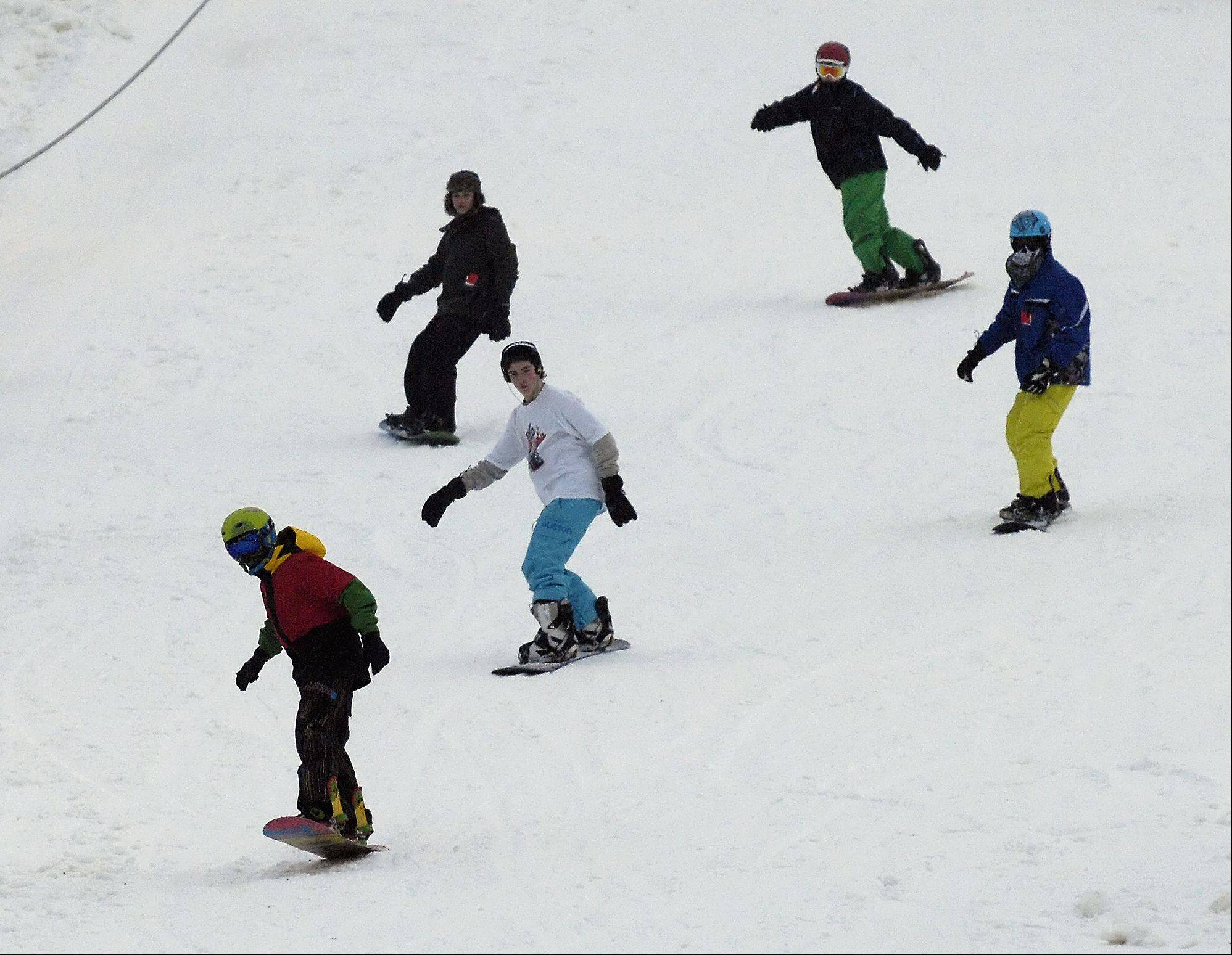 A group of snowboarders hit the slopes at Four Lake Ski Area in Lisle Thursday.