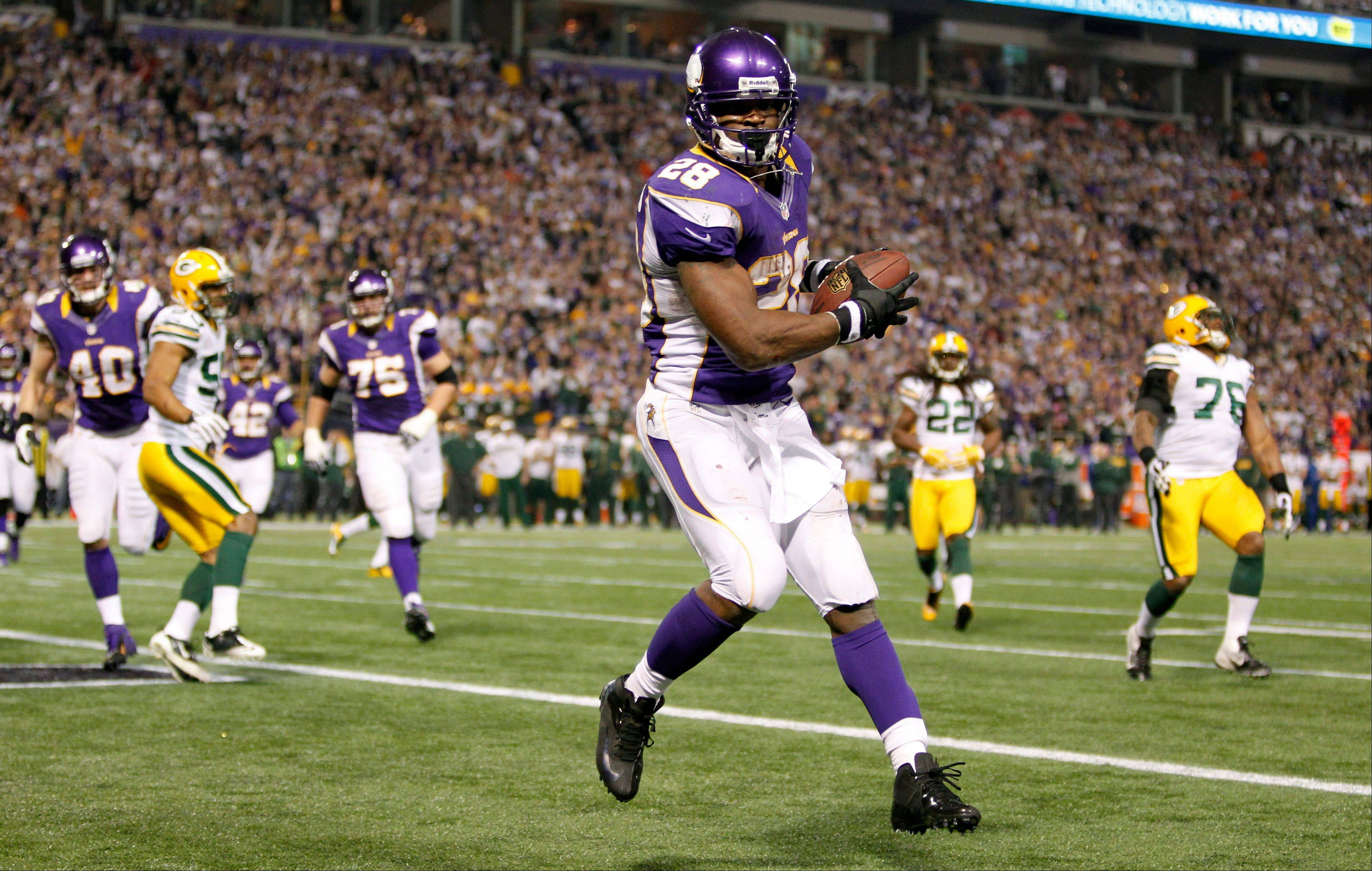 Minnesota Vikings running back Adrian Peterson catches a two-yard touchdown pass during the second half of an NFL football game against the Green Bay Packers Sunday, Dec. 30, 2012, in Minneapolis.