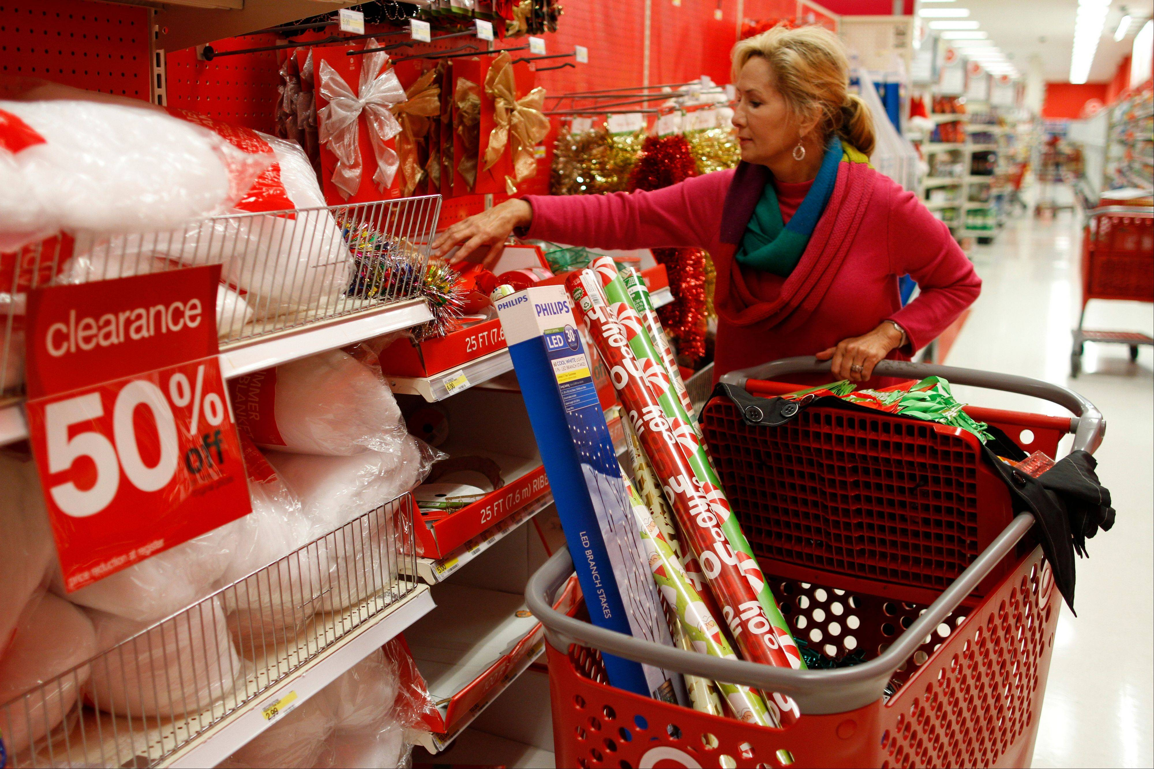 Holly Bryan stocks up on Christmas wrapping paper and other holiday items while shopping the day after Christmas deals at a Target store in Chattanooga, Tenn. Wednesday.