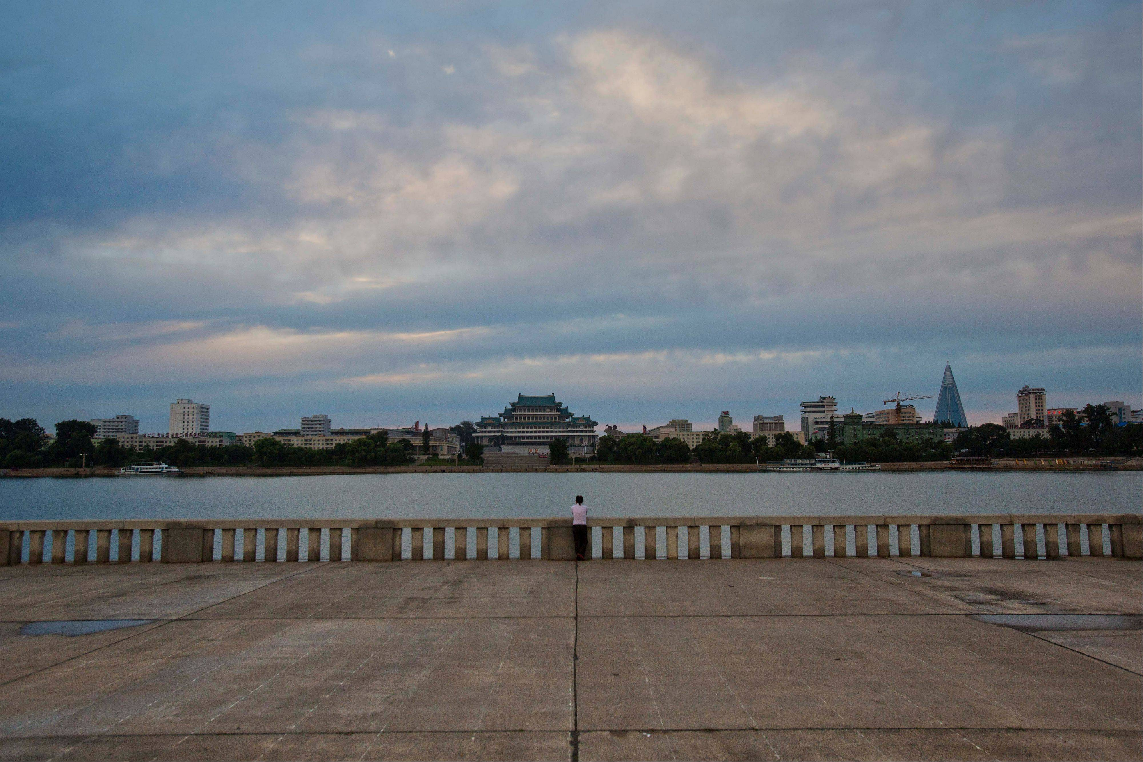A woman stands along the bank of the Taedong River at the en
