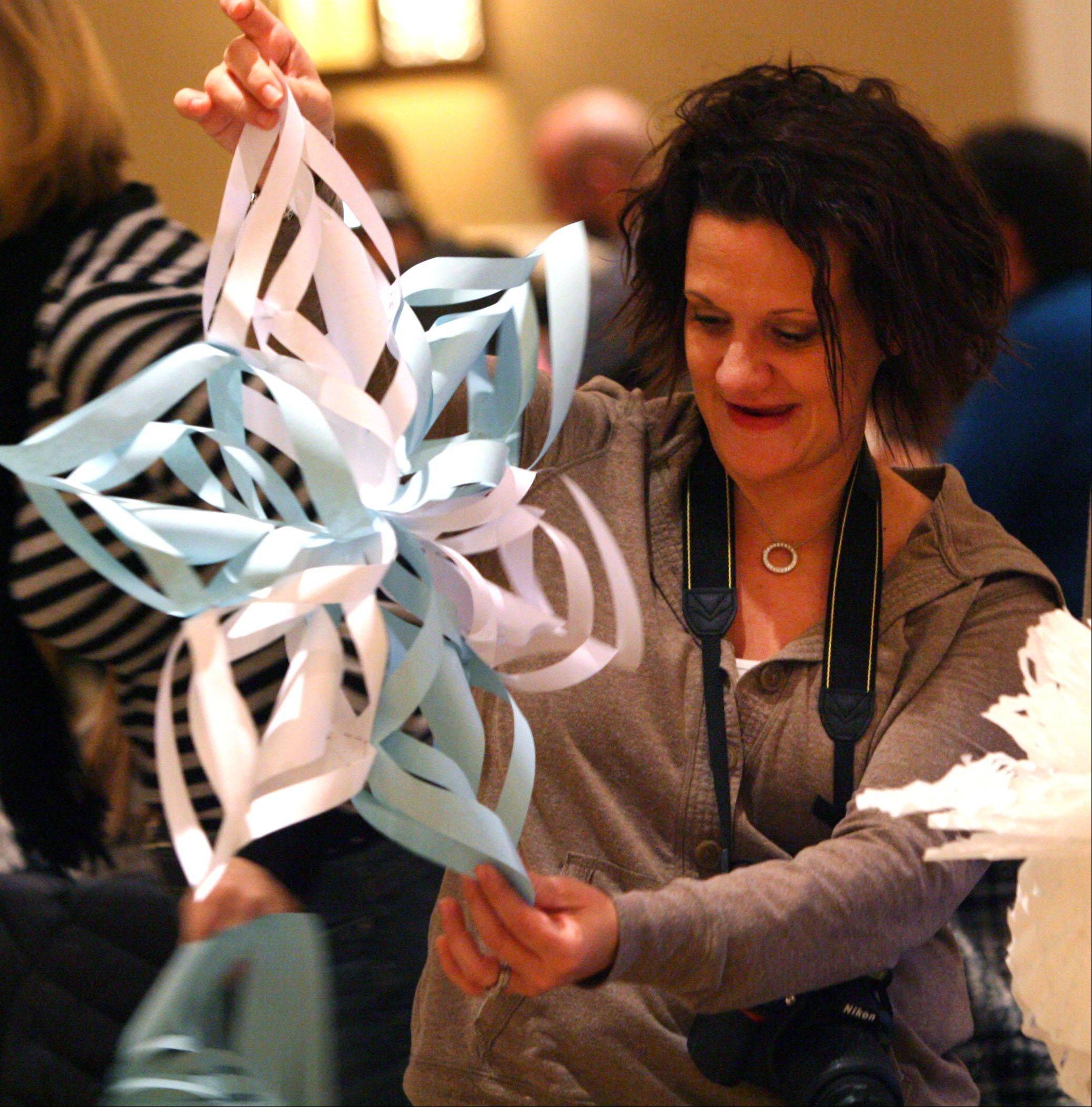 Organizer Lora Rampino, of Lake Zurich, holds up a 3-D snowflake made by a volunteer as people banded together to create snowflakes for the kids of Sandy Hook Elementary School in Connecticut. About 200 people showed up to Concord Banquets in Lake Zurich for the snowflake making effort. An estimated 5000 snowflakes were made.