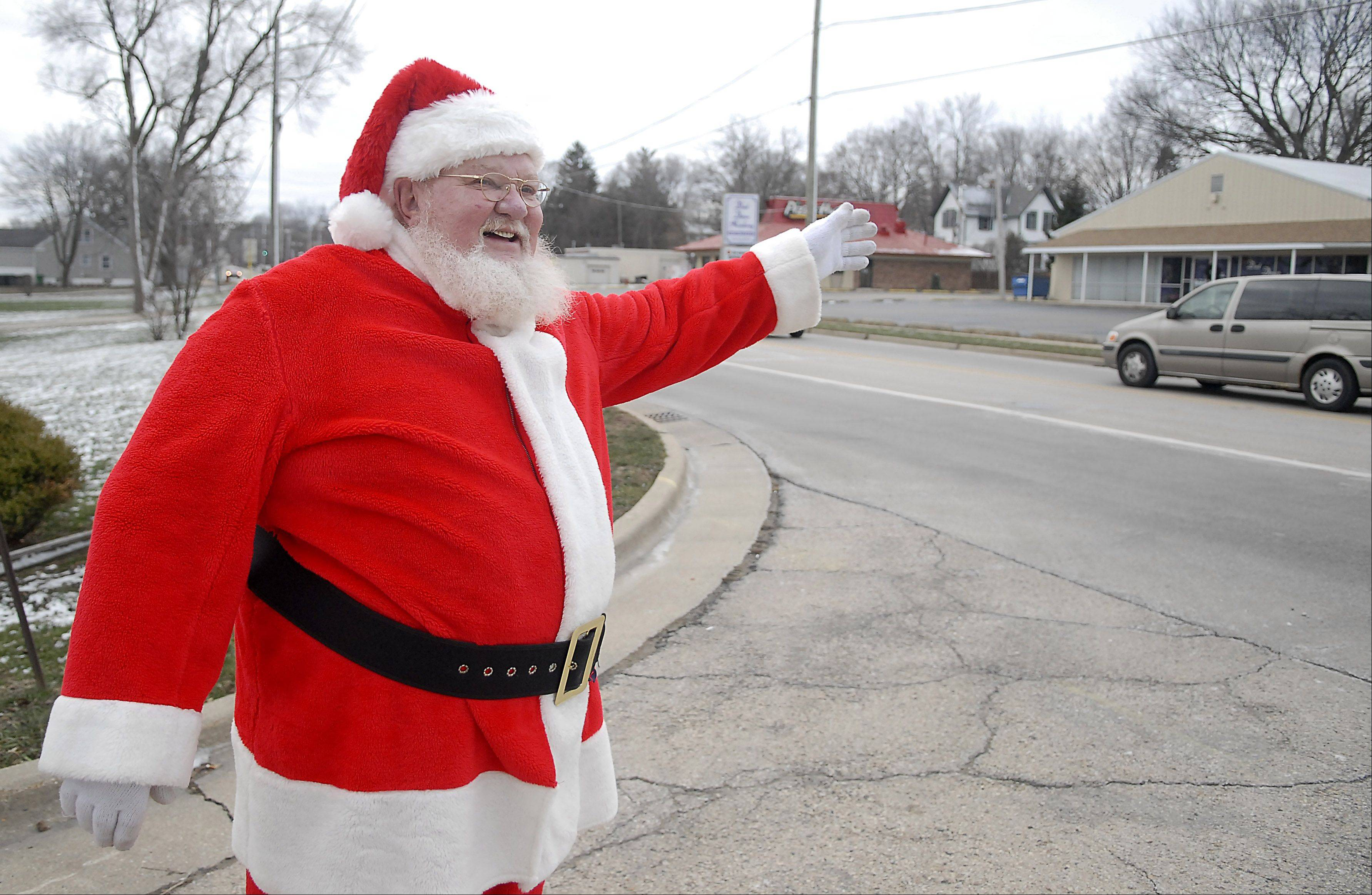 Richard Ahrens, of East Dundee, waves to travelers on the corner of Rt. 31 and Stone Street in South Elgin on Christmas Day. 20 years ago, Ahrens lived in a home at this corner and found himself bored after his children moved away, so he decided to dress up like Santa and wave to people on the road. He stands out there no matter rain, sleet, or snow for about three hours. People come to take pictures with him, bring him coffee or just honk and say Merry Christmas.