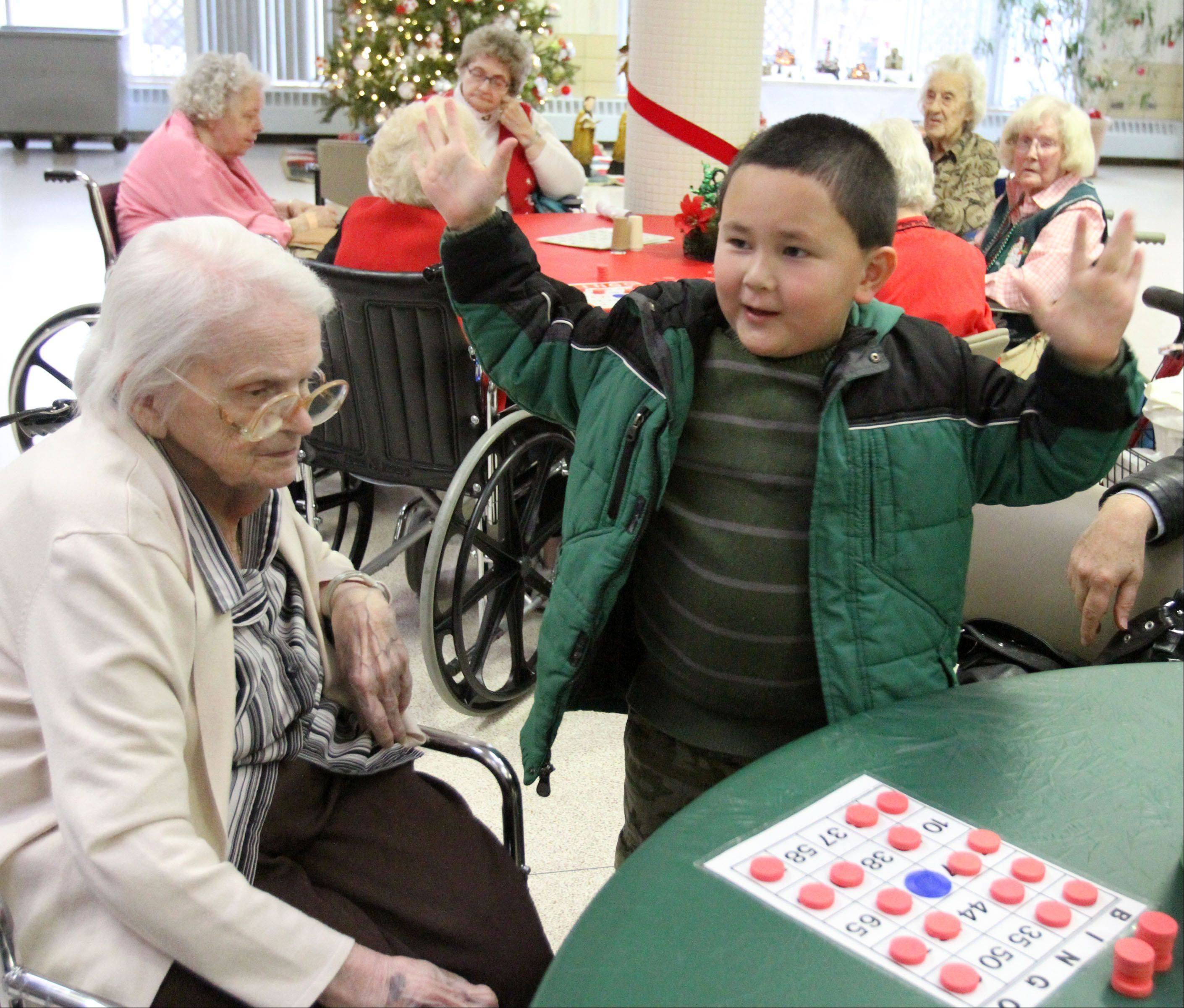 Bin Healy, 5, of Mundelein, celebrates as his grandmother Ann Healy wins a bingo game at the Lake County owned Winchester House nursing home on Christmas Day in Libertyville.