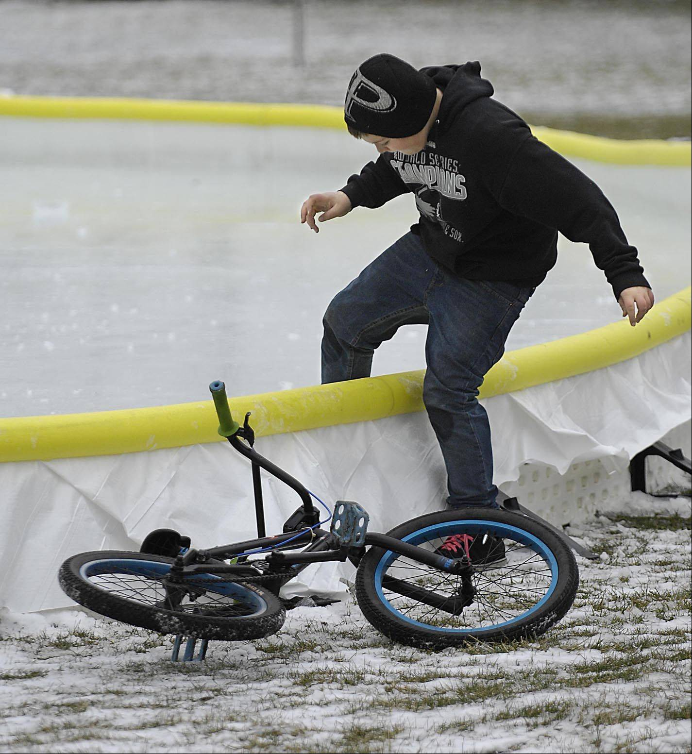 Curtis Bergstrom steps carefully over the edge of a temporary ice rink in County Park in South Elgin Monday. He and neighborhood friend Alex Bowers rode their bikes to the park and spent time sliding on the thin ice. They are both 12 and said the ice cracked as they walked.