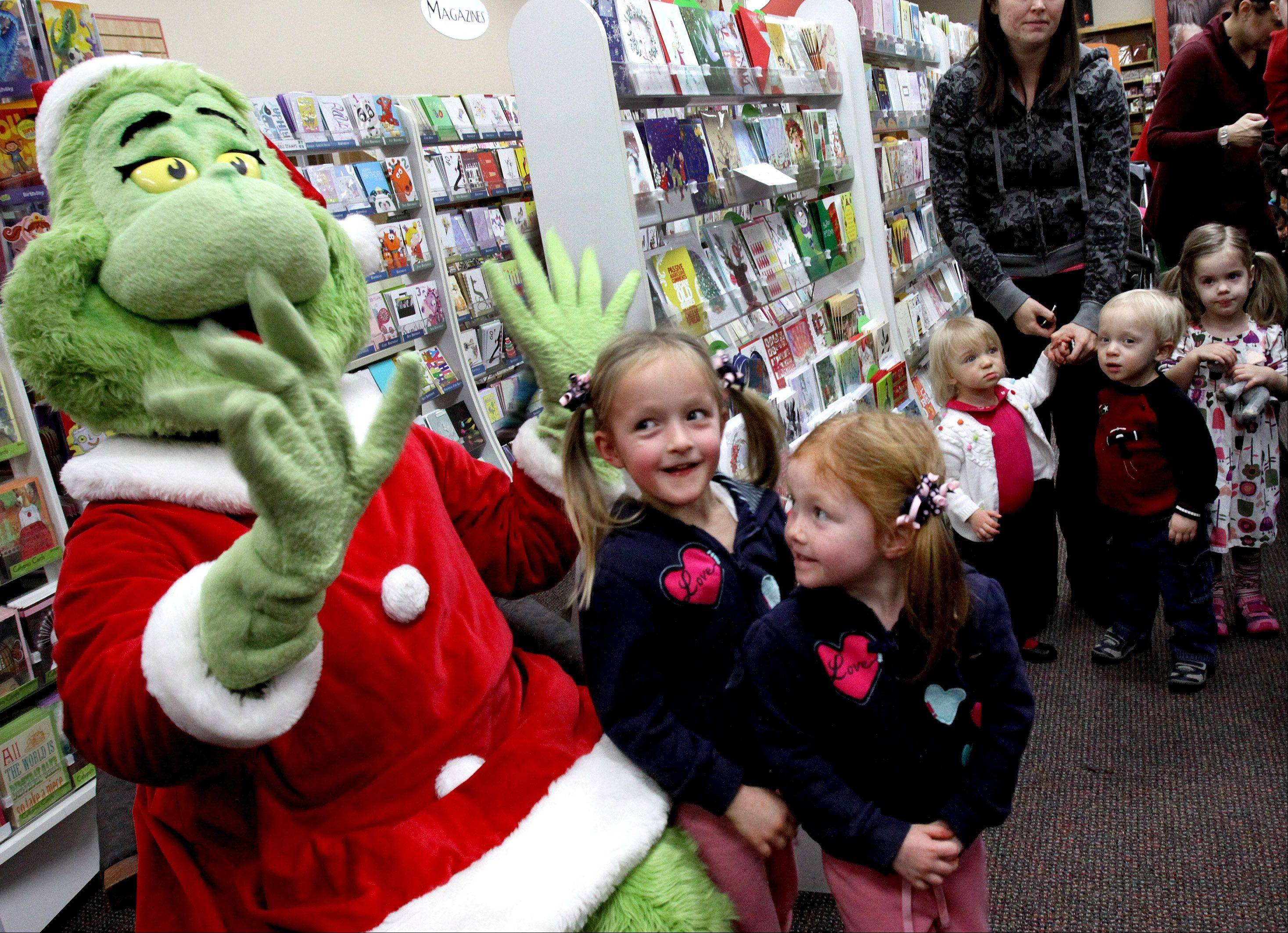Four-year-old twins Emily, left, and Abigail Schiltz, of Naperville, meet the Grinch as other kids wait their turn to pose for photos, at Anderson's Bookshop in Naperville Friday.