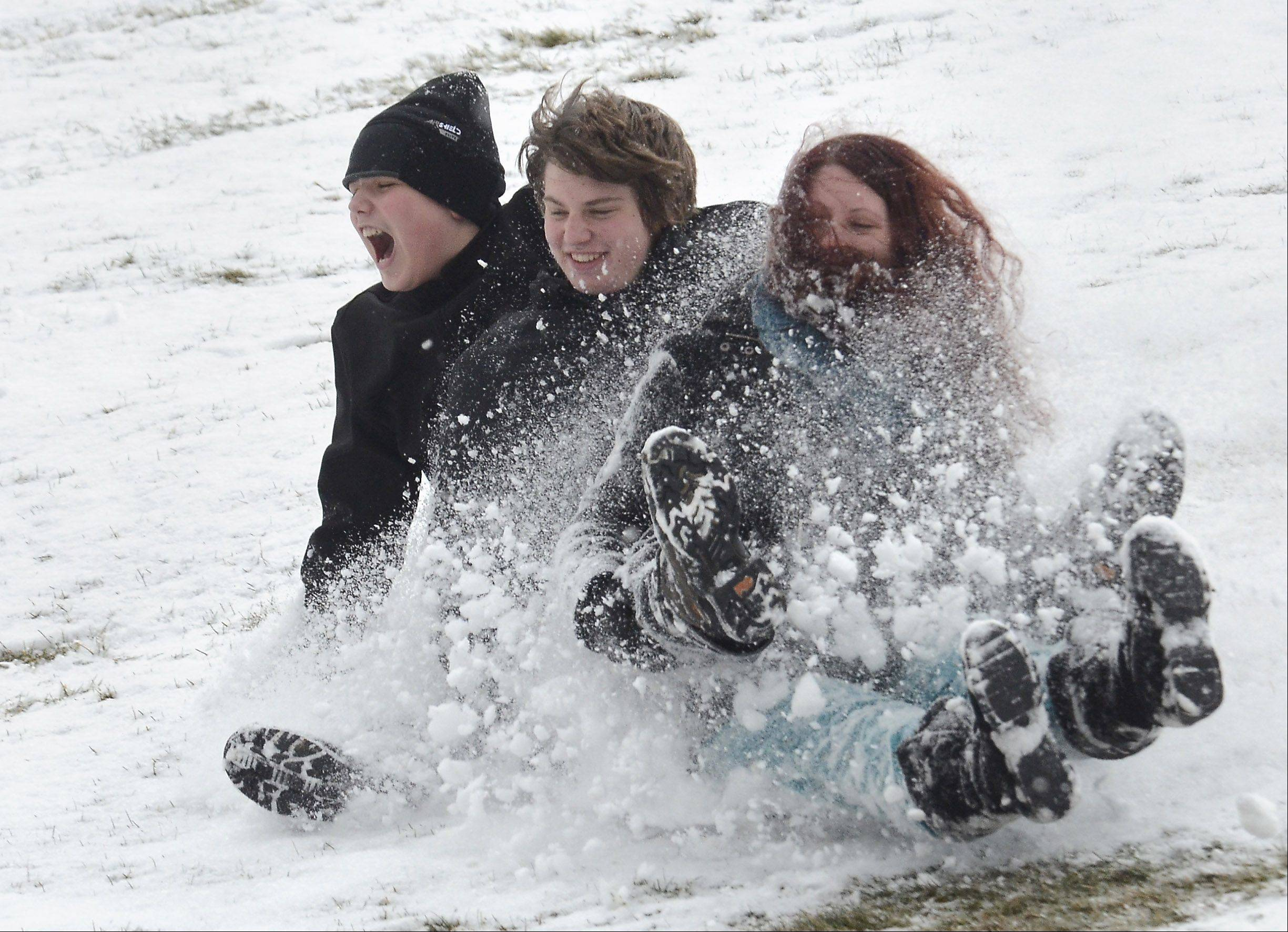 Noah Walter, 13, Kyle Walter, 15, and Jordan Walter, 21, all of Arlington Heights, get a wild ride on the sled hill at Sunset Meadows Park Friday in Arlington Heights.