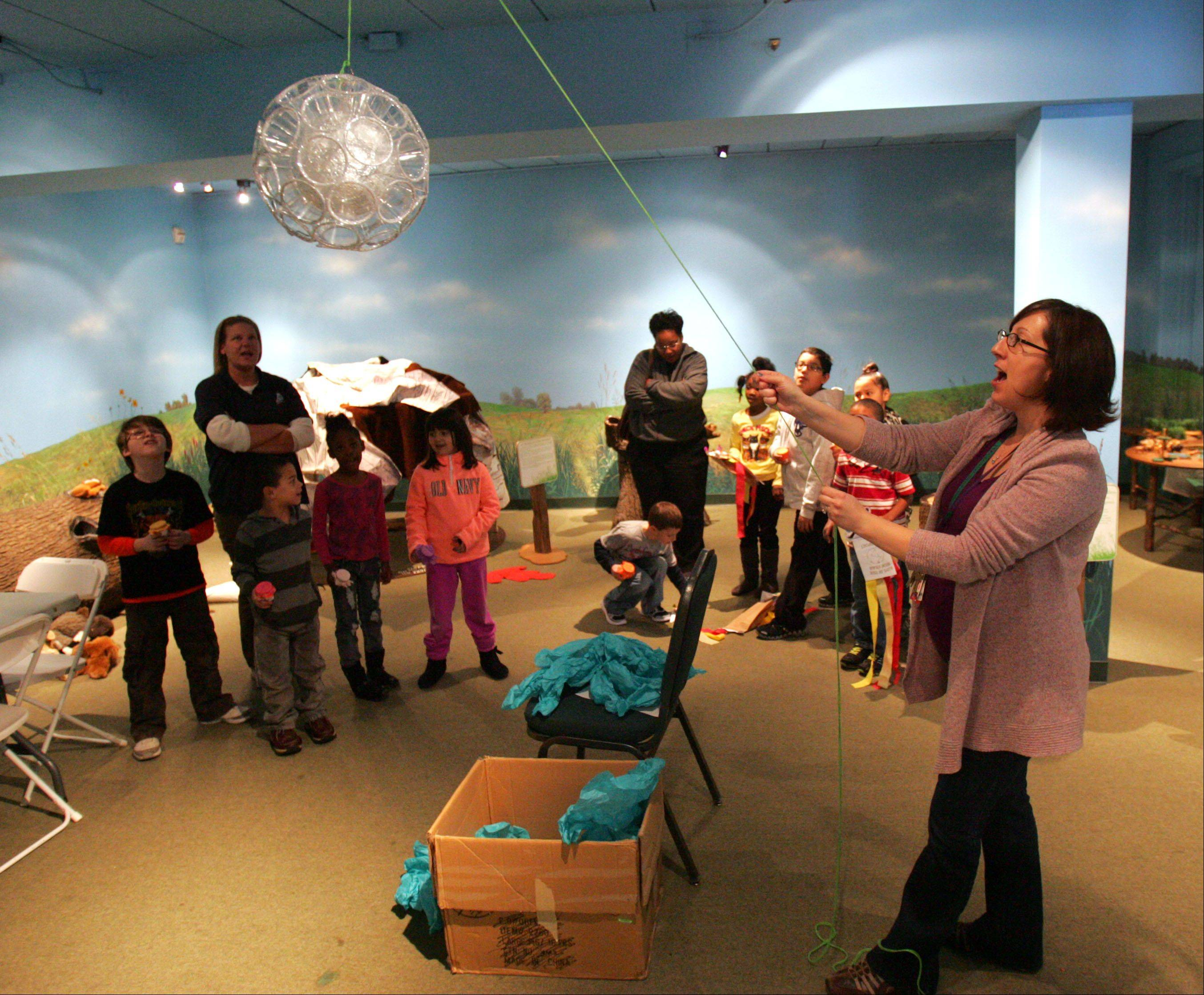 Educator Seleena Kuester performs a ball drop as kids learned about New Year's customs from around the world at the Lake County Discovery Museum in Wauconda Thursday.
