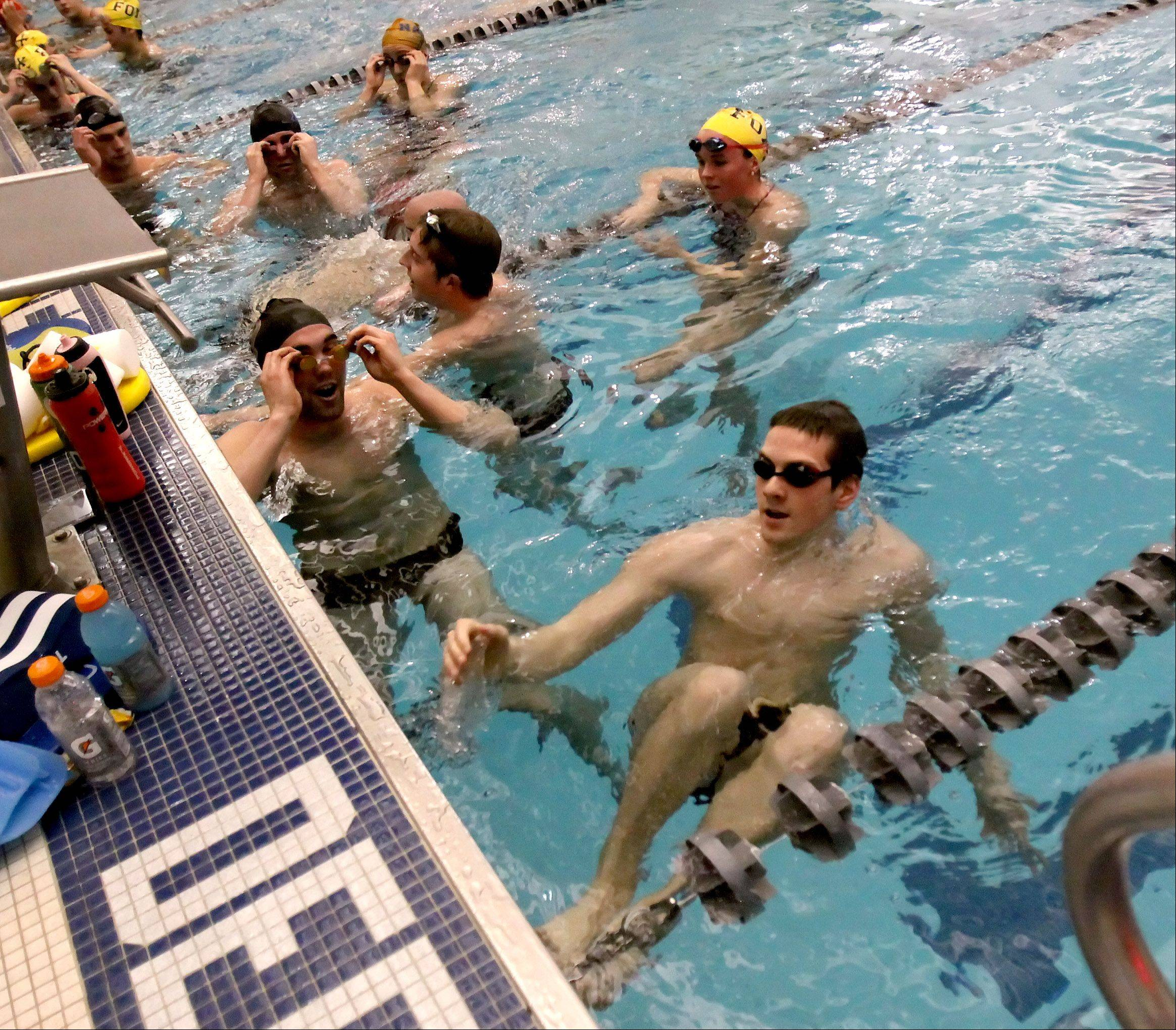 Grant Betulius, right, Neuqua Valley High School graduate and current student at the University of Iowa, trains with other former area high school swimmers and possible future Olympians at his alma mater Wednesday during their holiday break.