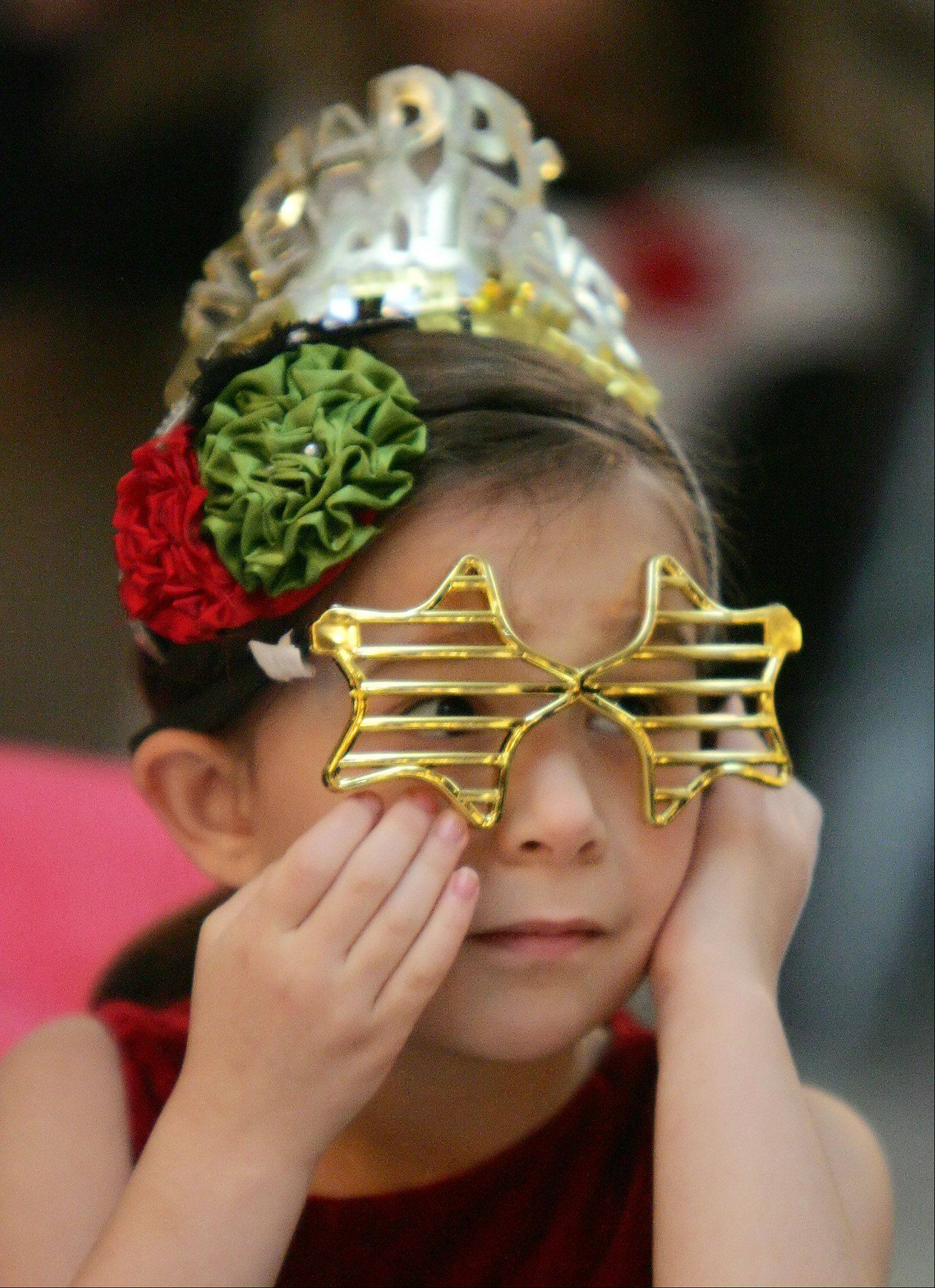 Kaia Mavradas, 5, of Mount Prospect, wears a party hat and glasses during the New Year's Eve-Eve Celebration Sunday at Bristol Court Banquets in Mount Prospect. The Mount Prospect Downtown Merchants Association hosted the fifth annual party for all ages.