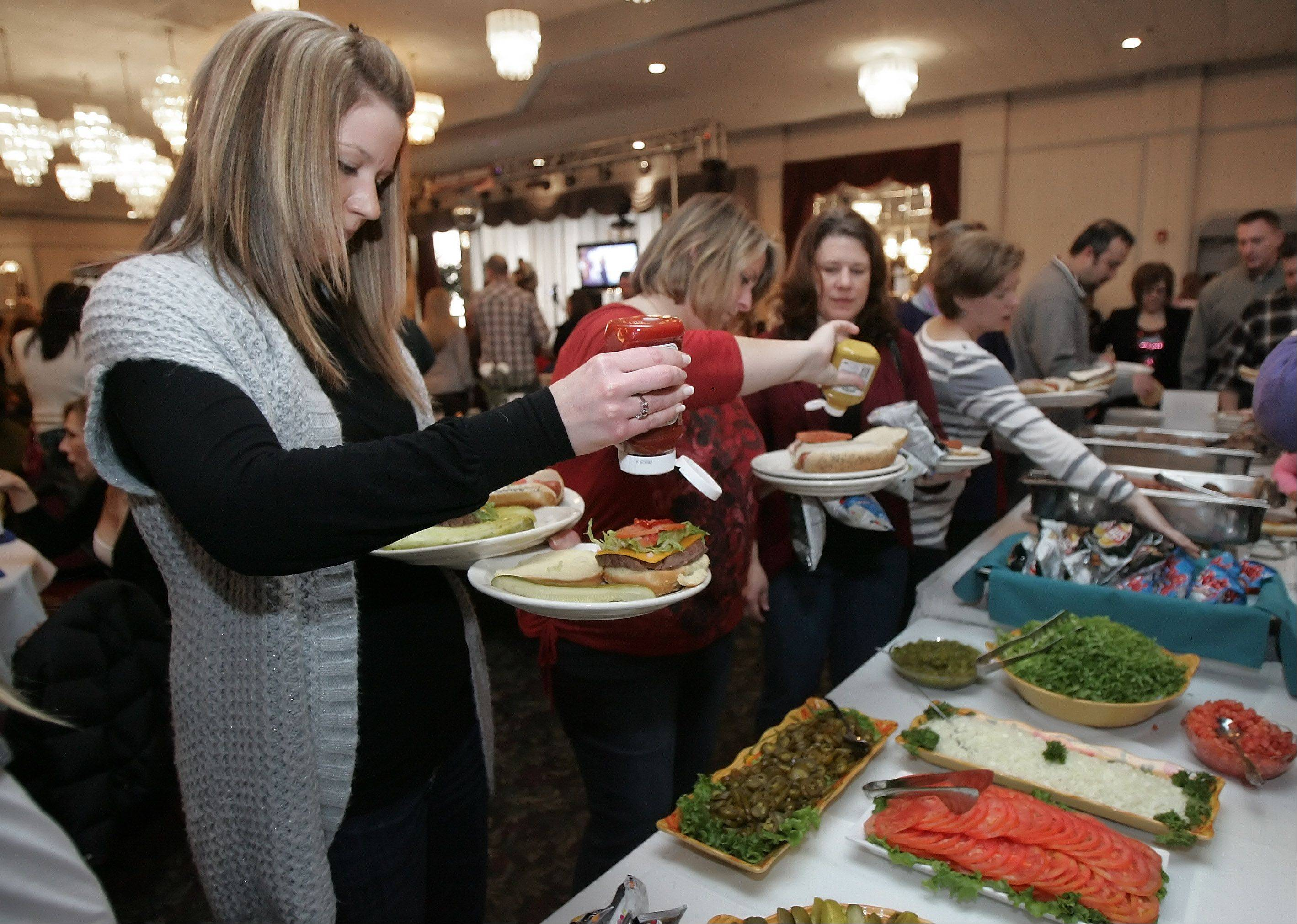 Michelle Zalewski, of Wheeling, holds three plates of food for her children during the New Year's Eve-Eve Celebration Sunday at Bristol Court Banquets in Mount Prospect. The Mount Prospect Downtown Merchants Association hosted the fifth annual party for all ages.