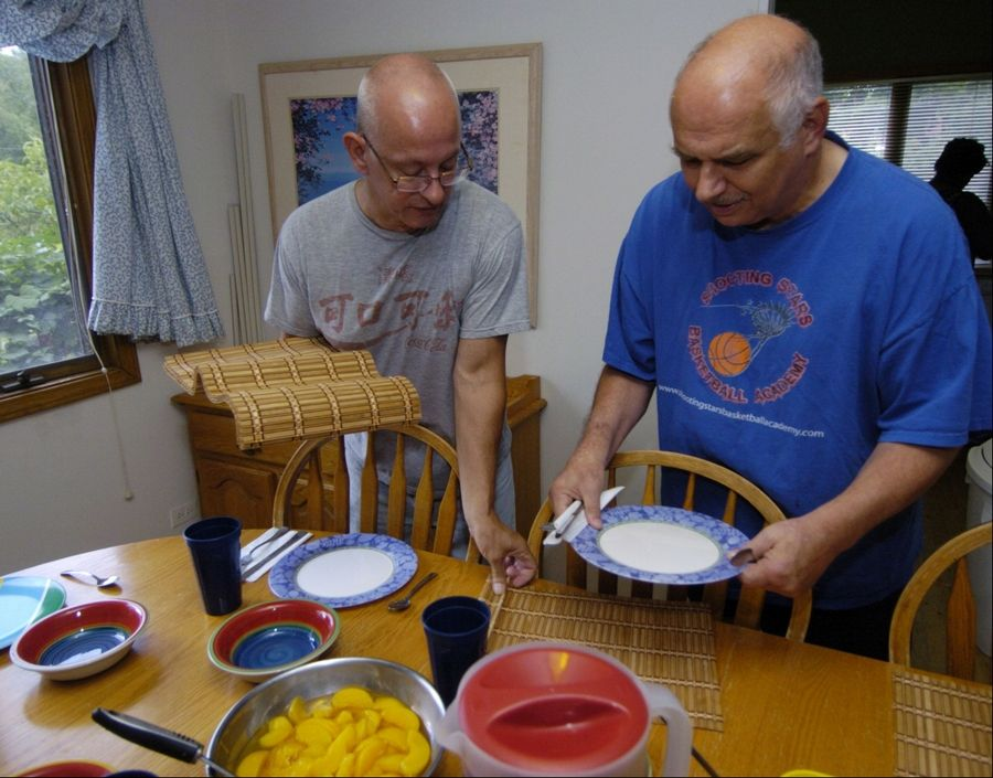 Little City Residential Assistant Howard Rogers helps resident Steve Bloom as he sets the table for dinner at a group home in Palatine for developmentally and intellectually disabled men.