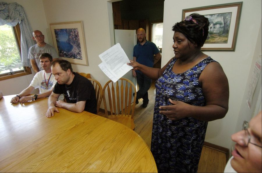 Little City Residential Assistant Belinda Mason discusses the events of the day with residents gathered at the kitchen table of a group home in Palatine for developmentally and intellectually disabled men.