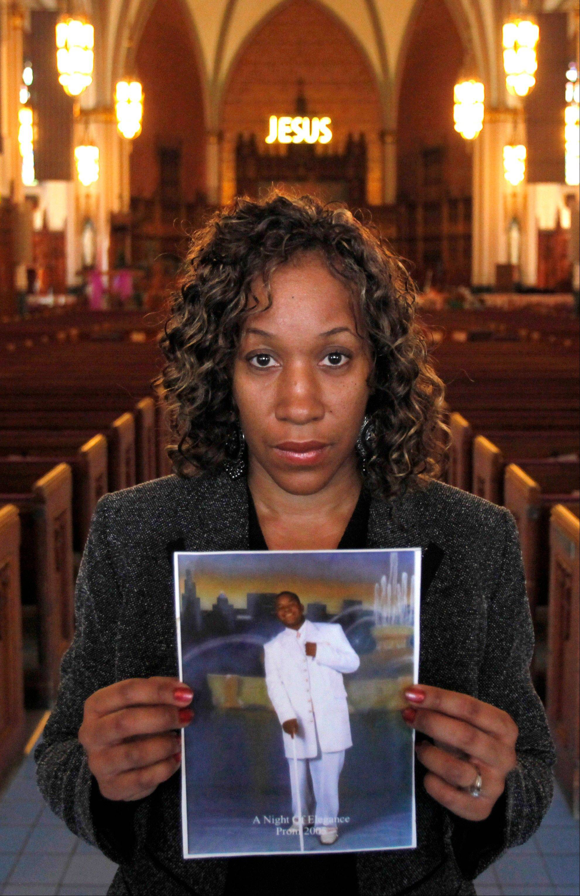 Pam Bosley stands inside the Chicago's St. Sabina Catholic Church and poses with a photograph of her son, Terrell, who was gunned down in 2006. Bosley now works with kids 14 to 21 at the church, teaching them life and leadership skills and ways to reduce violence.