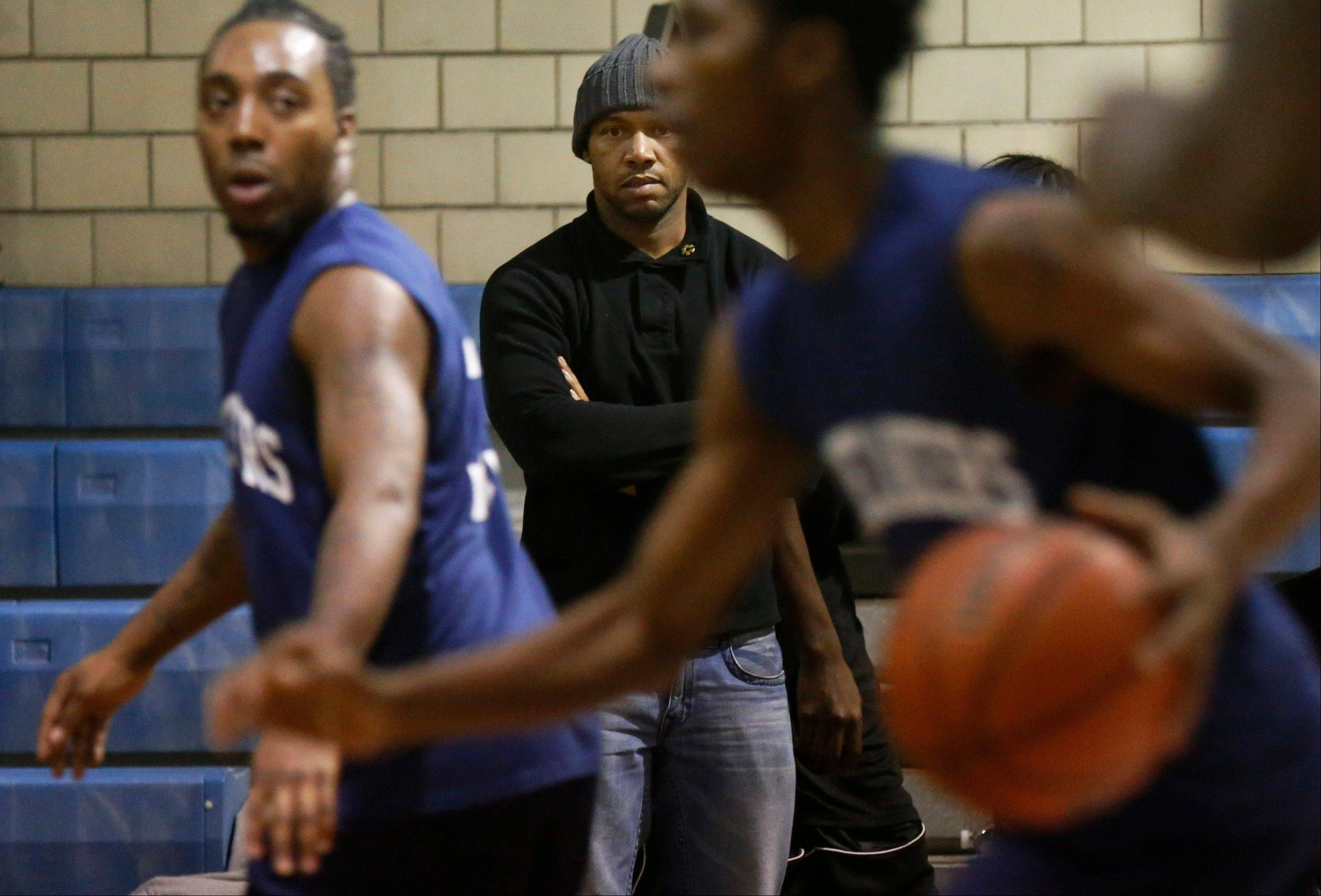 Curtis Toler watches his team participate in a basketball tournament for reputed gang members and associates earlier this month at the St. Sabina Catholic Church in the Auburn-Gresham neighborhood on Chicago's South Side. Toler, 35, a former gang member and father of four, spent much of his life causing chaos. Now, he's preaching calm.