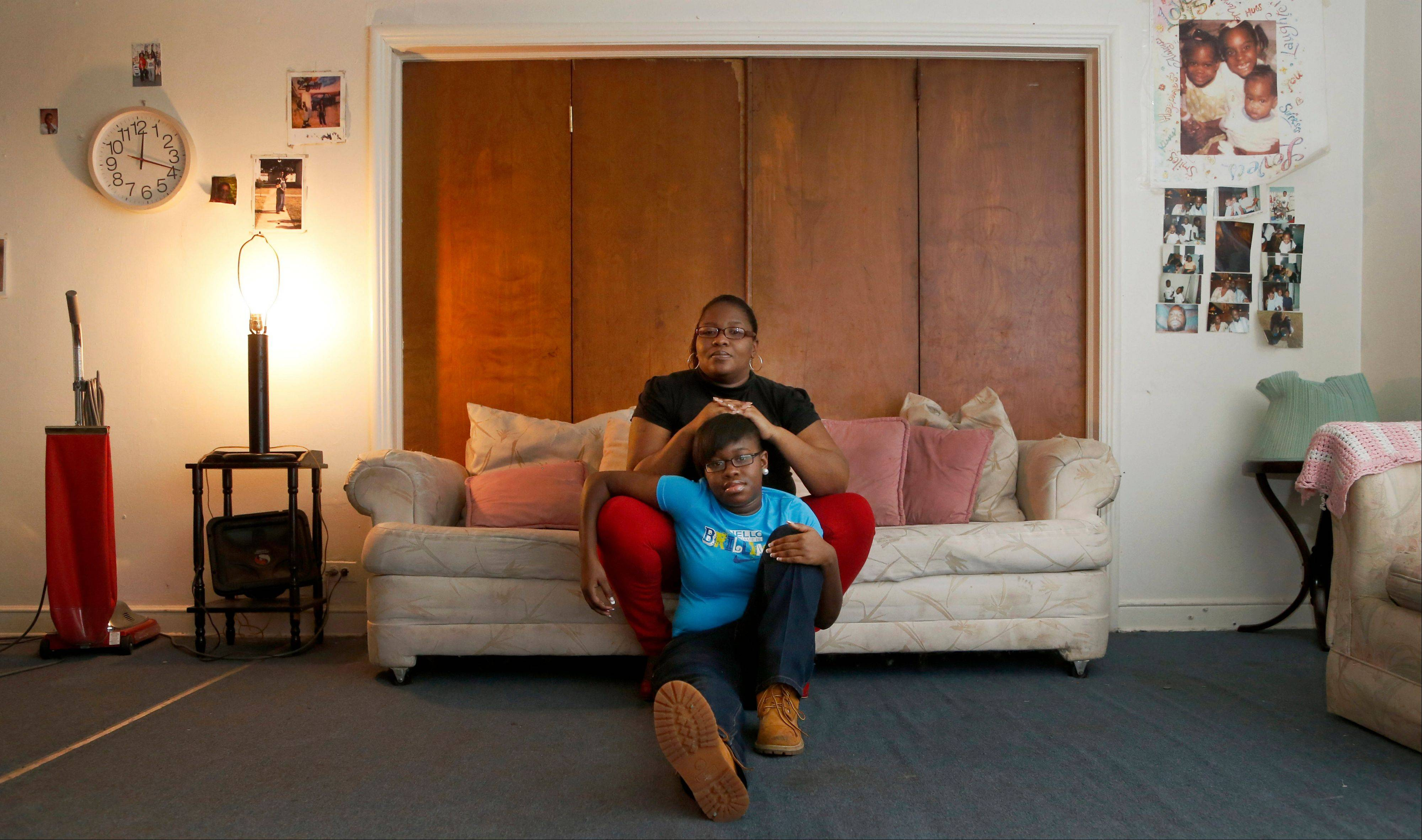 "Bobbie McComb sits on the sofa with her 14 year-old daughter, Cerria, at their home in the Auburn-Gresham neighborhood of Chicago's South Side. In the wrong place at the right time, Cerria and a friend were wounded when gunfire aimed at a reputed gang member struck them, with a bullet exploding in Cerria's right leg. ""I'm angry,"" Mrs. McComb says. ""I'm frustrated. I'm tired of them shooting our kids, killing our kids, thinking they can get away with it."""