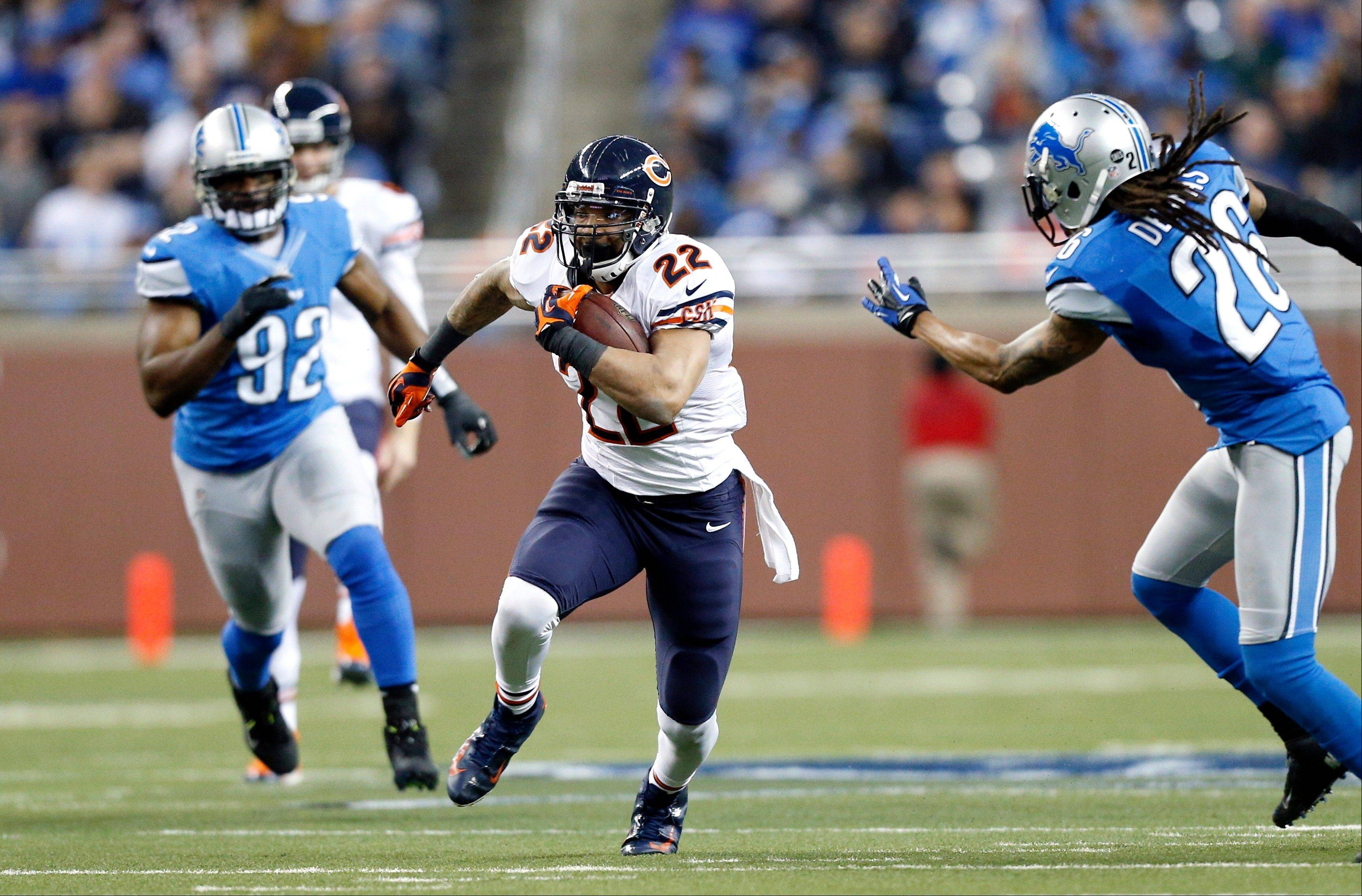 Chicago Bears running back Matt Forte (22) runs between Detroit Lions defensive end Cliff Avril (92) and free safety Louis Delmas (26) during the second quarter.