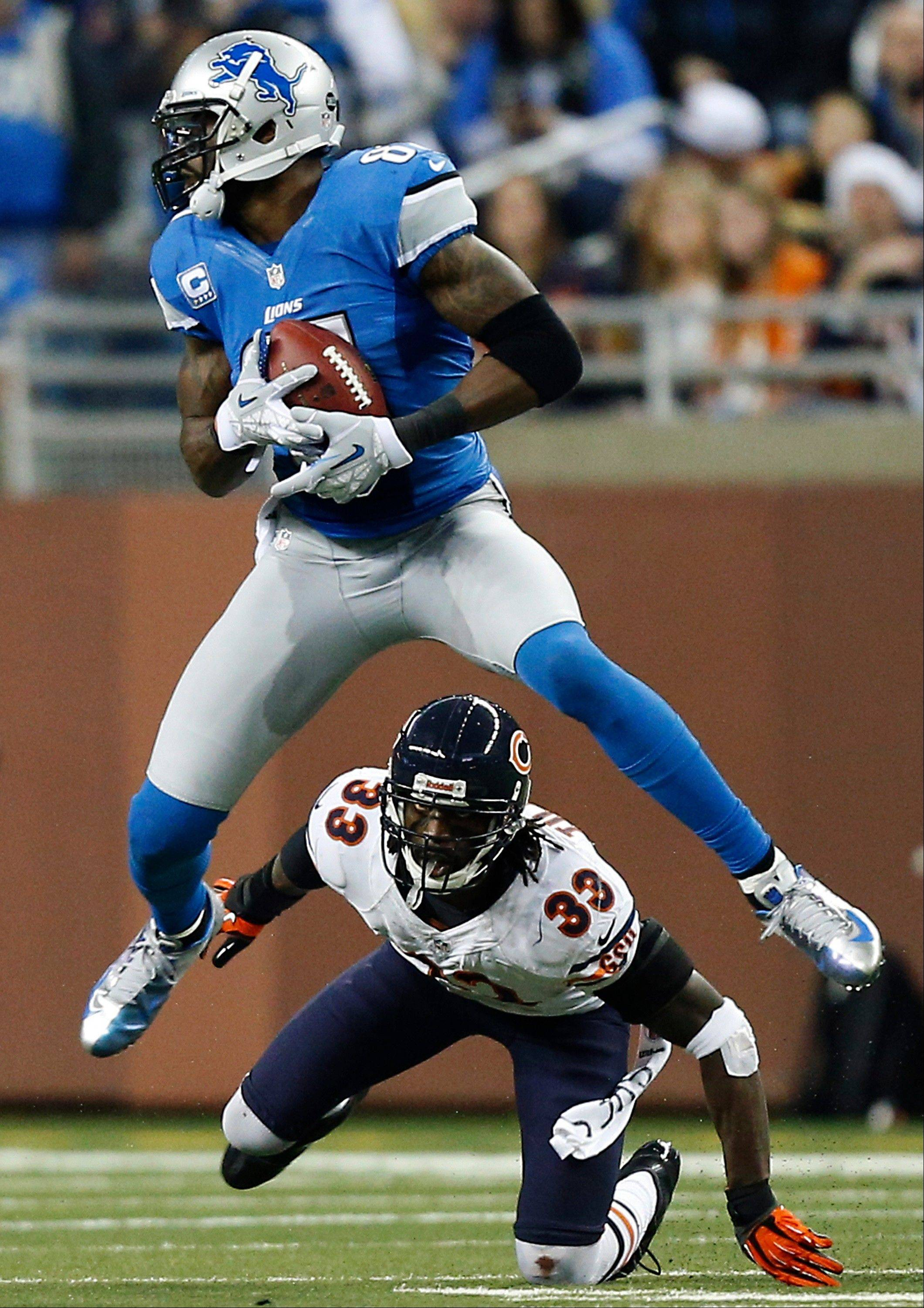 Detroit Lions wide receiver Calvin Johnson (81) gains 18-yards on a pass reception under pressure from Chicago Bears cornerback Charles Tillman (33) during the third quarter.