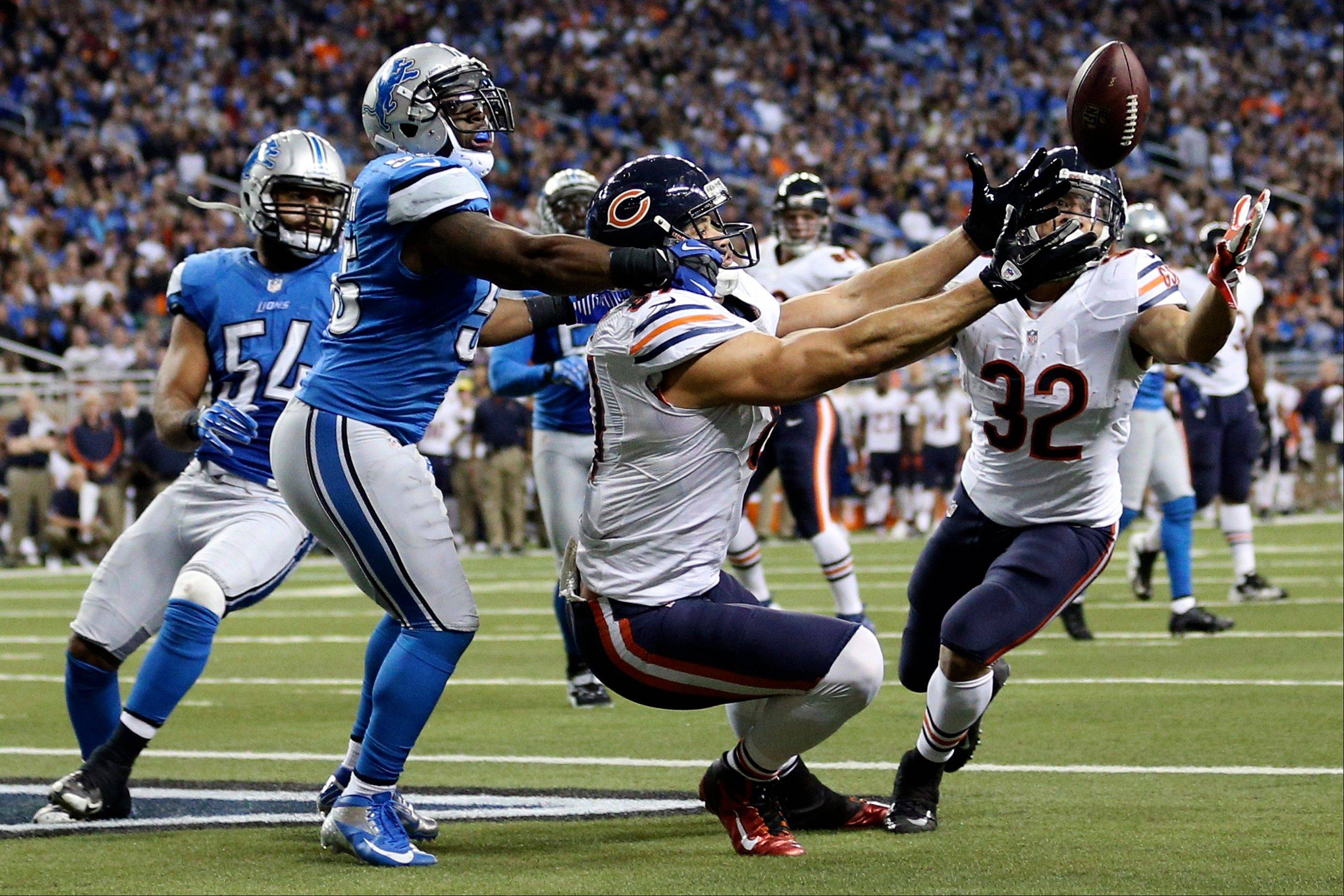 Detroit Lions middle linebacker Stephen Tulloch, left, breaks up a pass intended for Chicago Bears tight end Kellen Davis, center, during the fourth quarter. The Bears won 26-24.