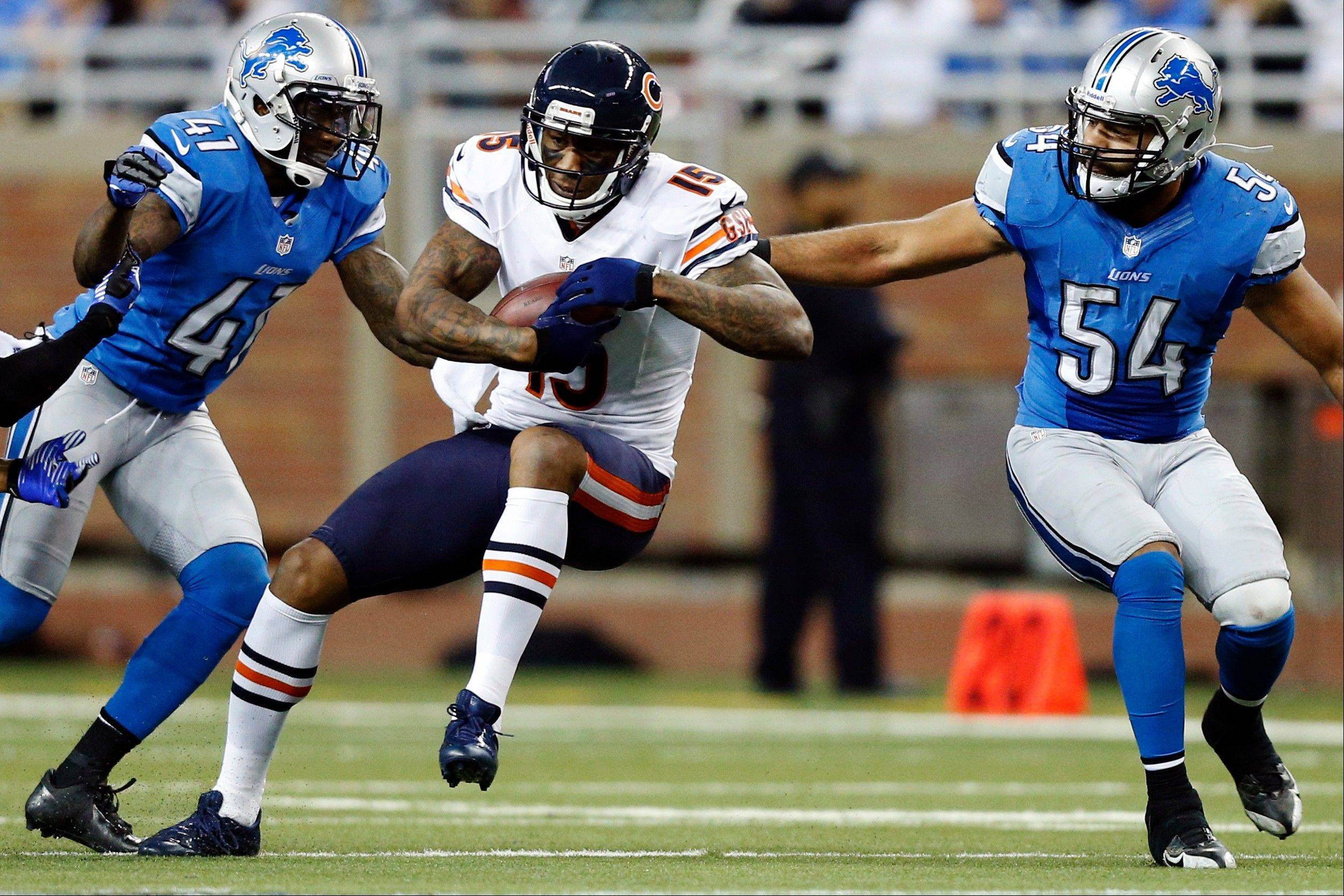 Chicago Bears wide receiver Brandon Marshall (15) makes a catch while defended by Detroit Lions cornerback Ron Bartell (41) and outside linebacker DeAndre Levy (54) during the fourth quarter. The Bears won 26-24.