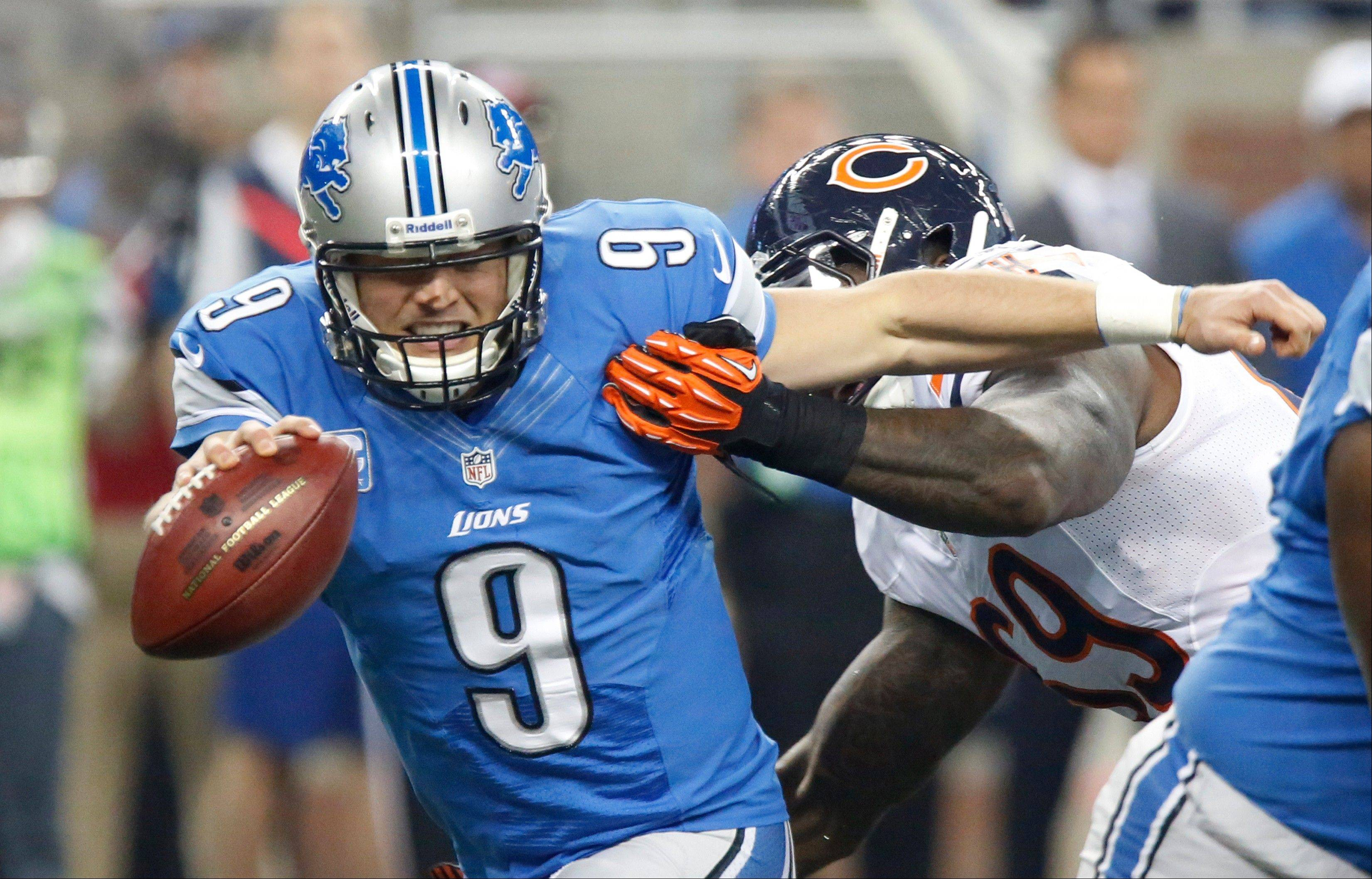 Detroit Lions quarterback Matthew Stafford (9) pulls away from Chicago Bears defensive tackle Henry Melton (69) during the first quarter.