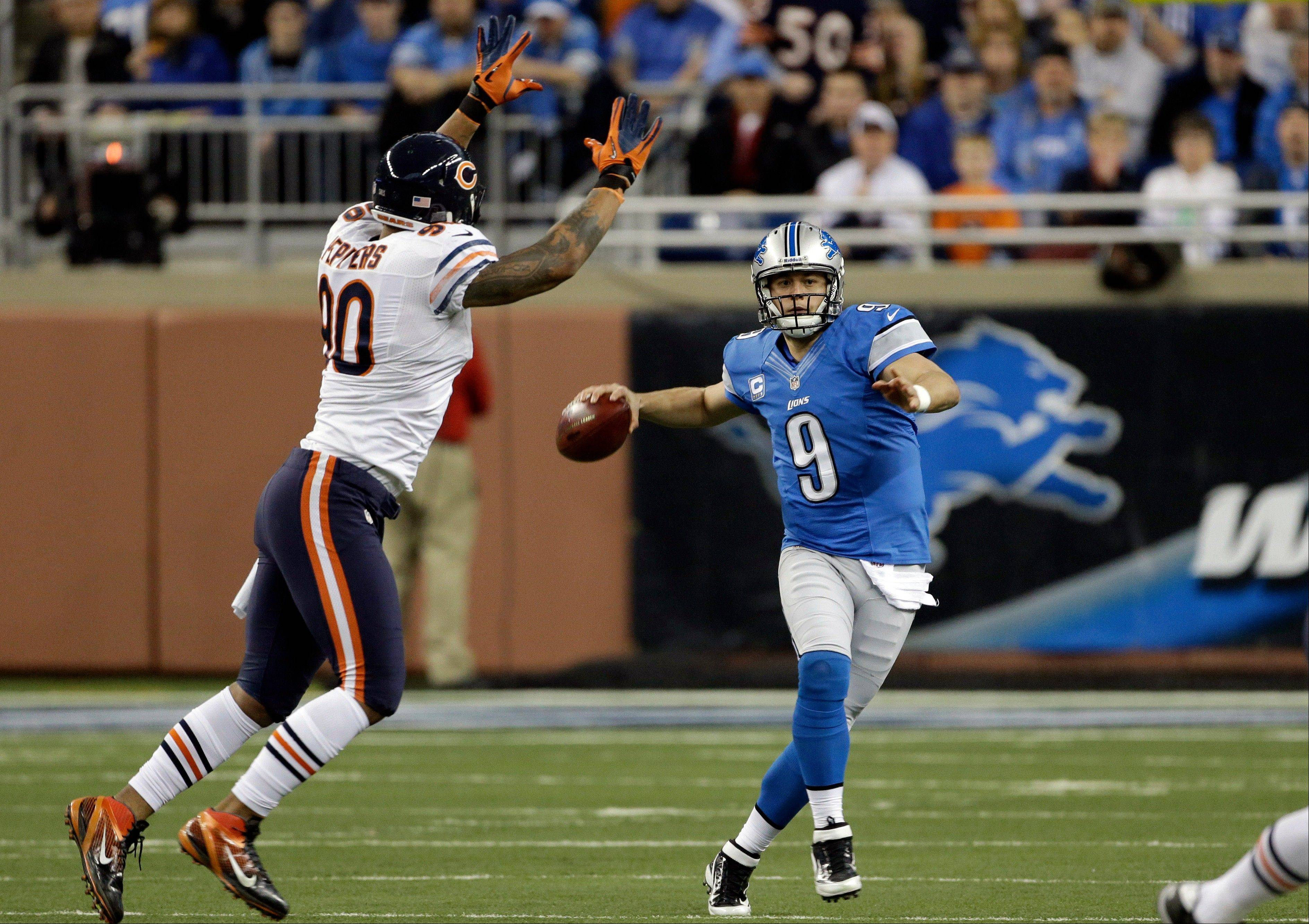Detroit Lions quarterback Matthew Stafford (9) looks downfield while chased by Chicago Bears defensive end Julius Peppers (90) during the first quarter.