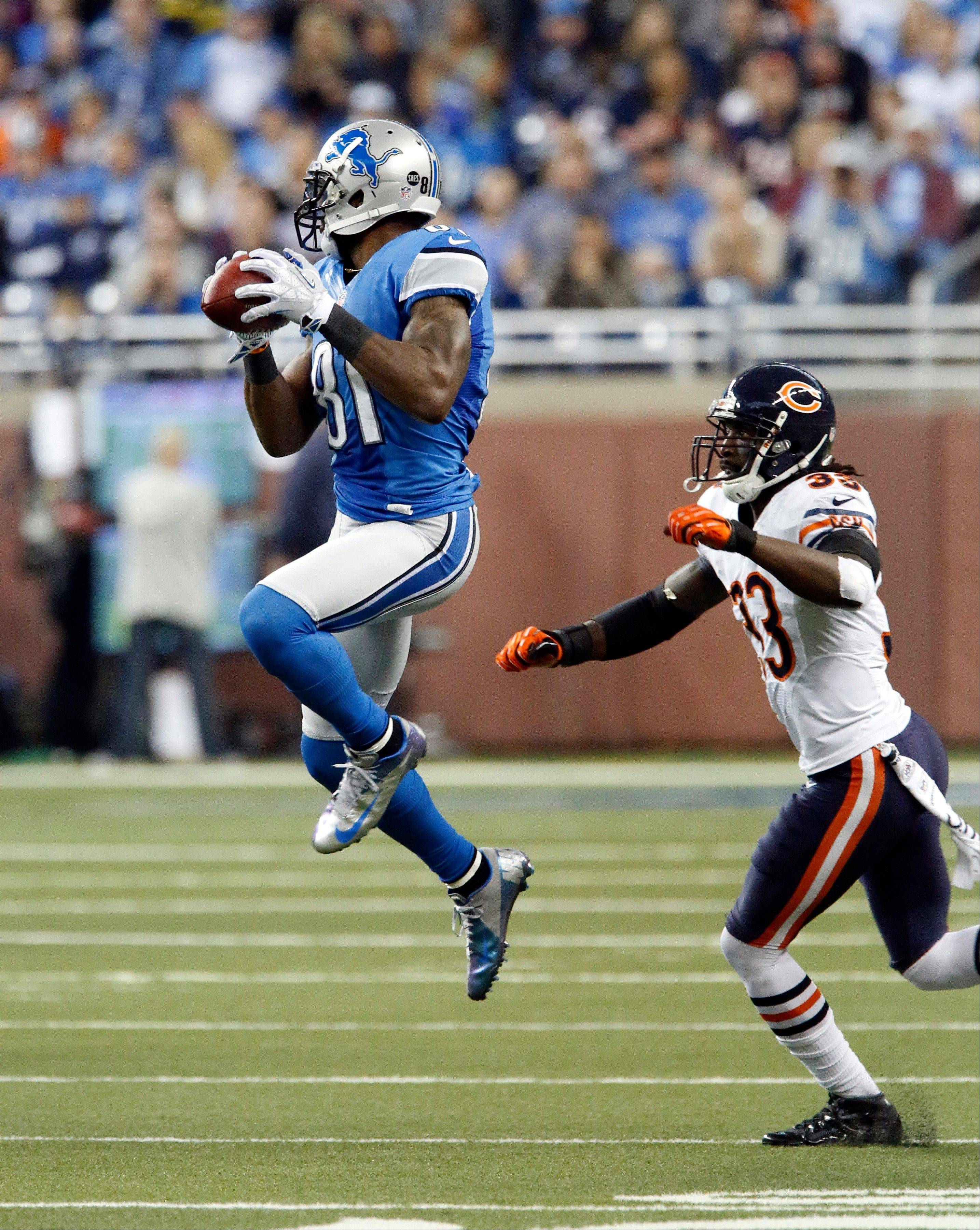 Detroit Lions wide receiver Calvin Johnson (81) makes a reception while defended by Chicago Bears cornerback Charles Tillman (33) during the first quarter.