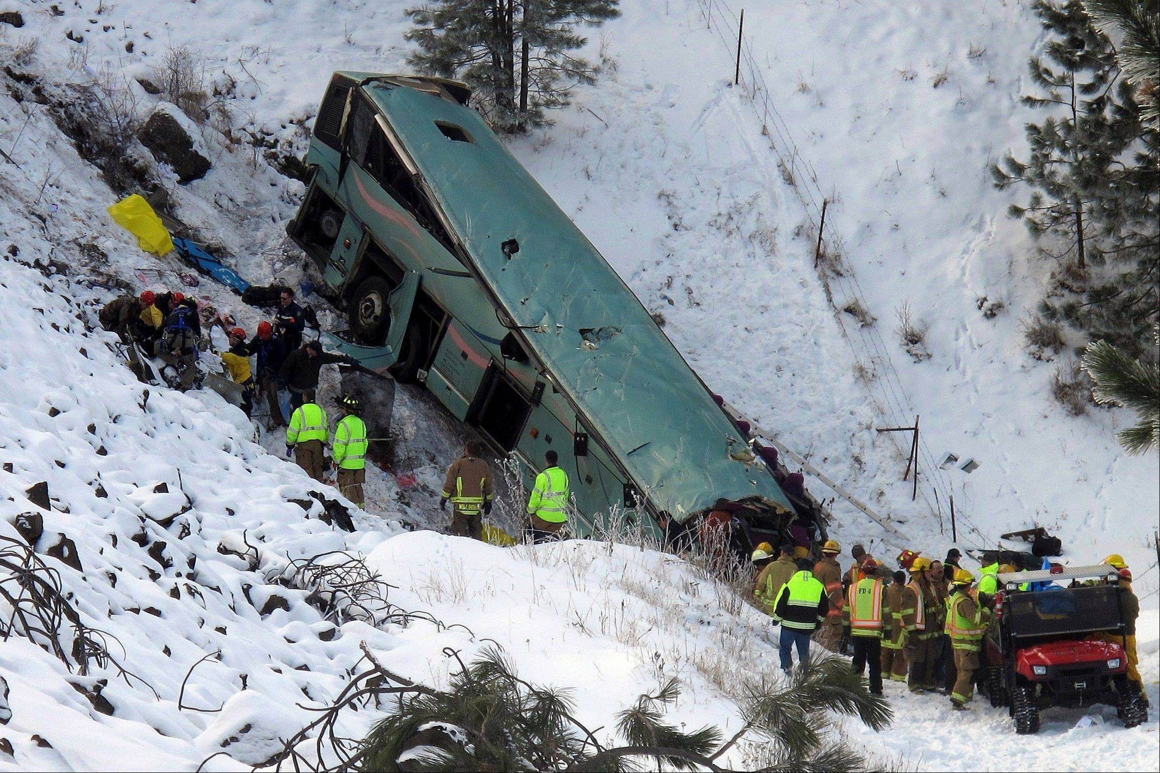 Emergency personnel respond to the scene of a multiple-fatality accident Sunday after a tour bus careened through a guardrail along an icy highway and fell several hundred feet down a steep embankment about 15 miles east of Pendleton, Ore., authorities said.