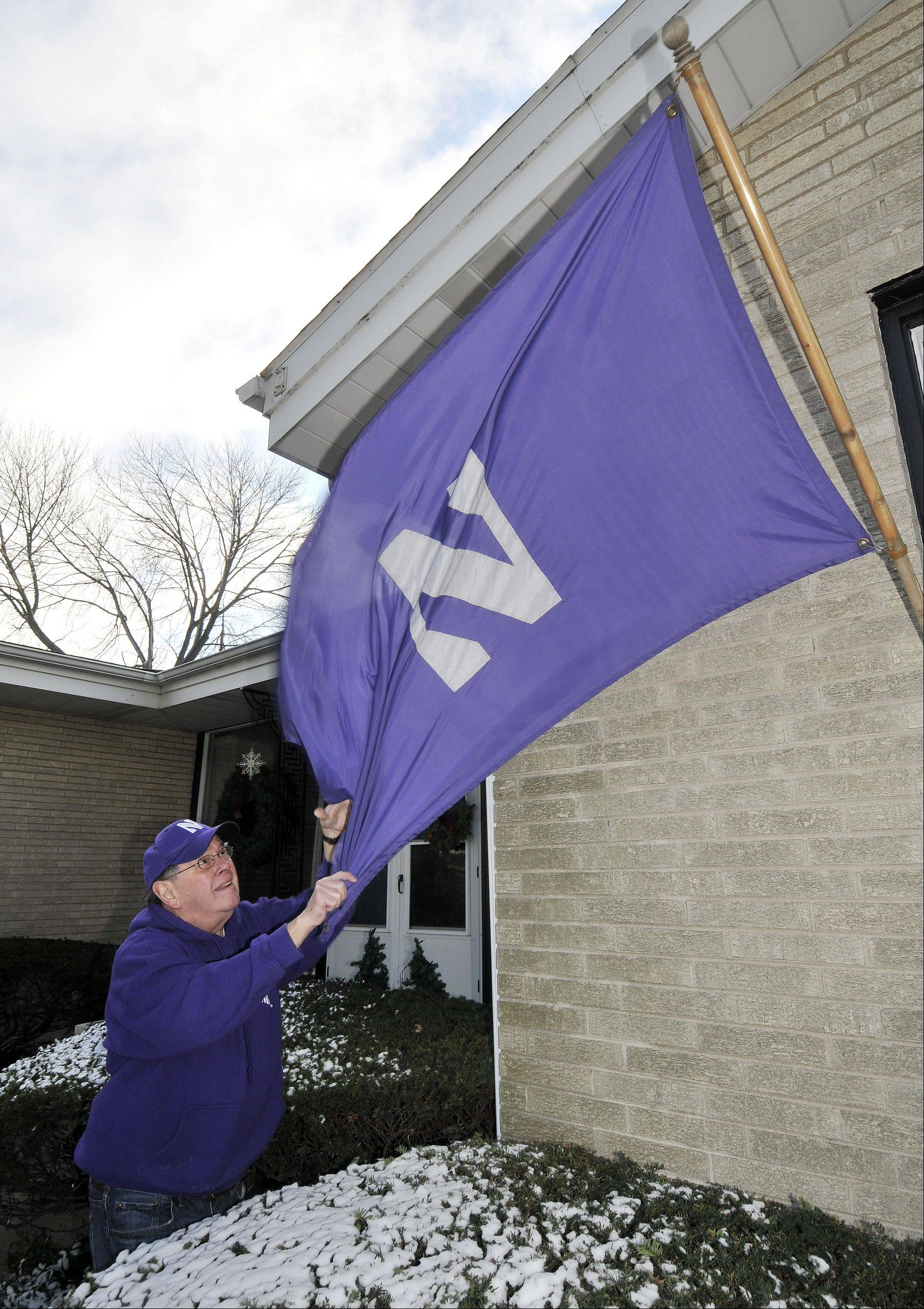 Retired neurosurgeon Dr. Tom Brown shows his purple pride as he unfurls his Northwestern flag at his Elmhurst home. He'll be in Florida to watch his team take on Mississippi State Jan. 1 in the Gator Bowl.