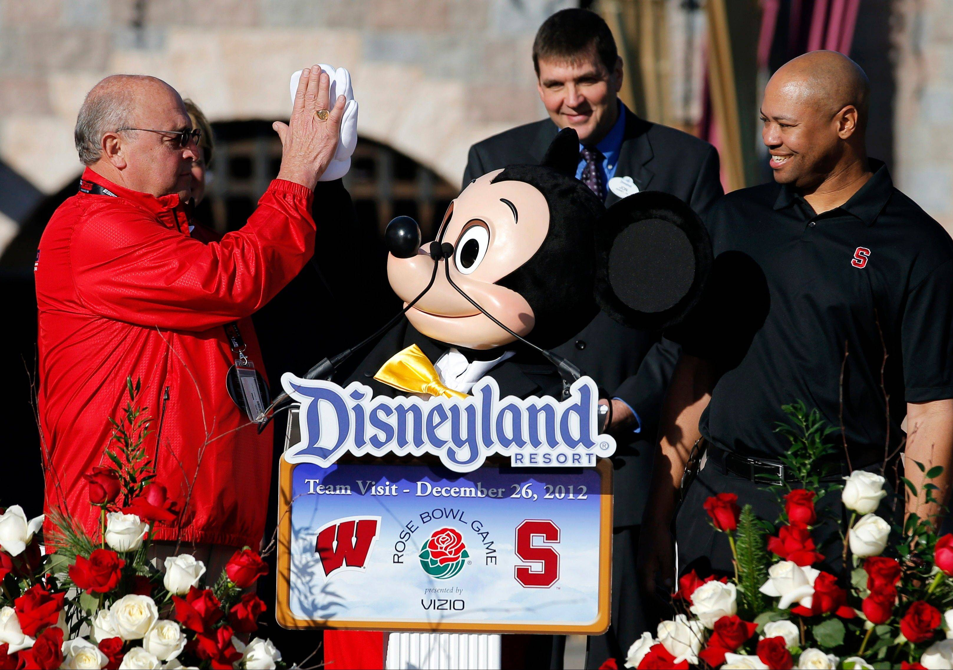 Wisconsin athletic director Barry Alvarez, left, gets a high-five from Mickey Mouse as Stanford coach David Shaw, right, watches. Alvarez will coach the Badgers in today's Rose Bowl against the Cardinal in Pasadenda, Calif.