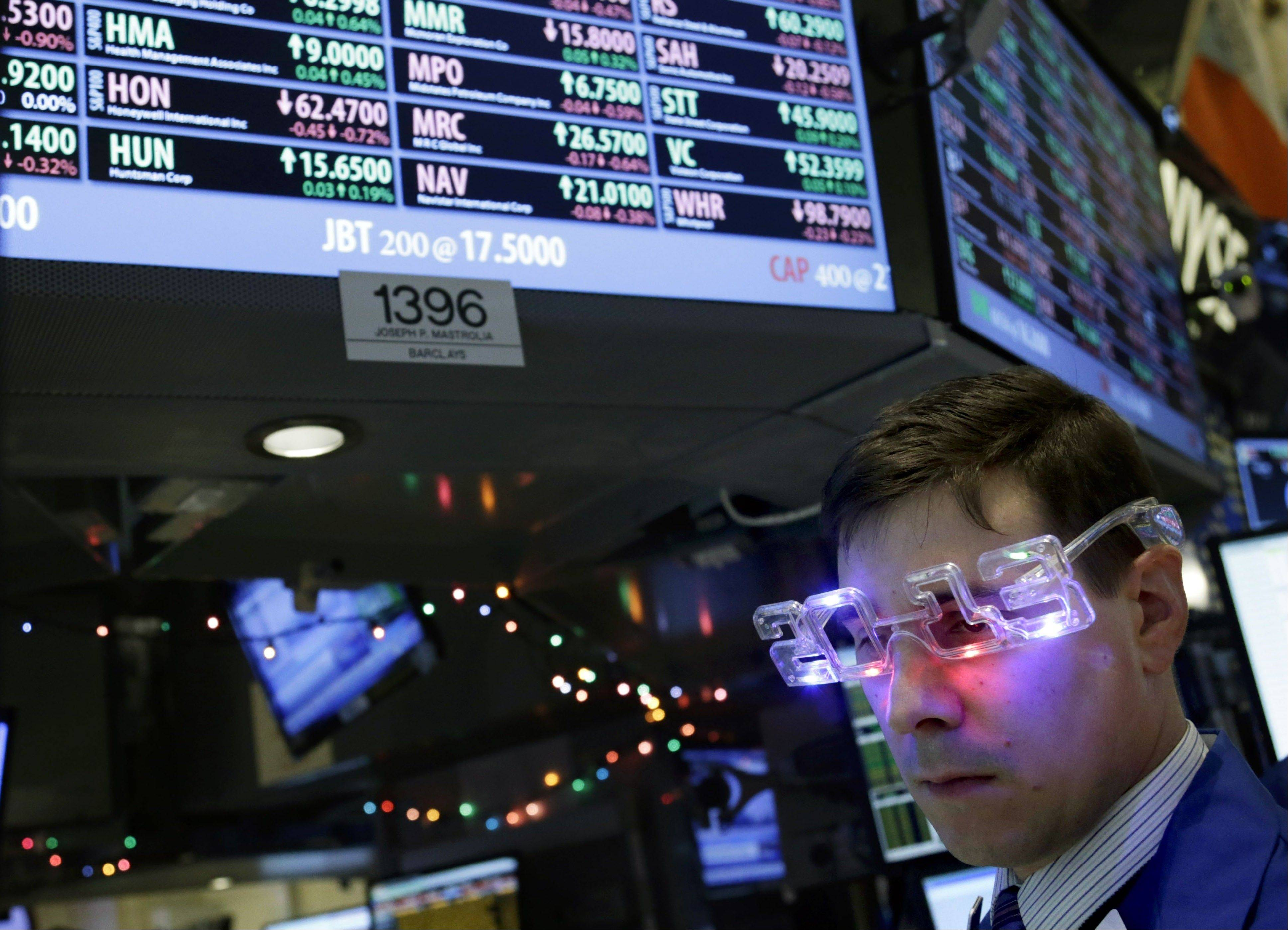 "A trader wearing ""2013"" glasses works on the floor at the New York Stock Exchange in New York on Monday. U.S. stocks surged on the last day of the year by the most since 1974 as Congress neared a deal to avert more than $600 billion in tax increases and spending cuts."