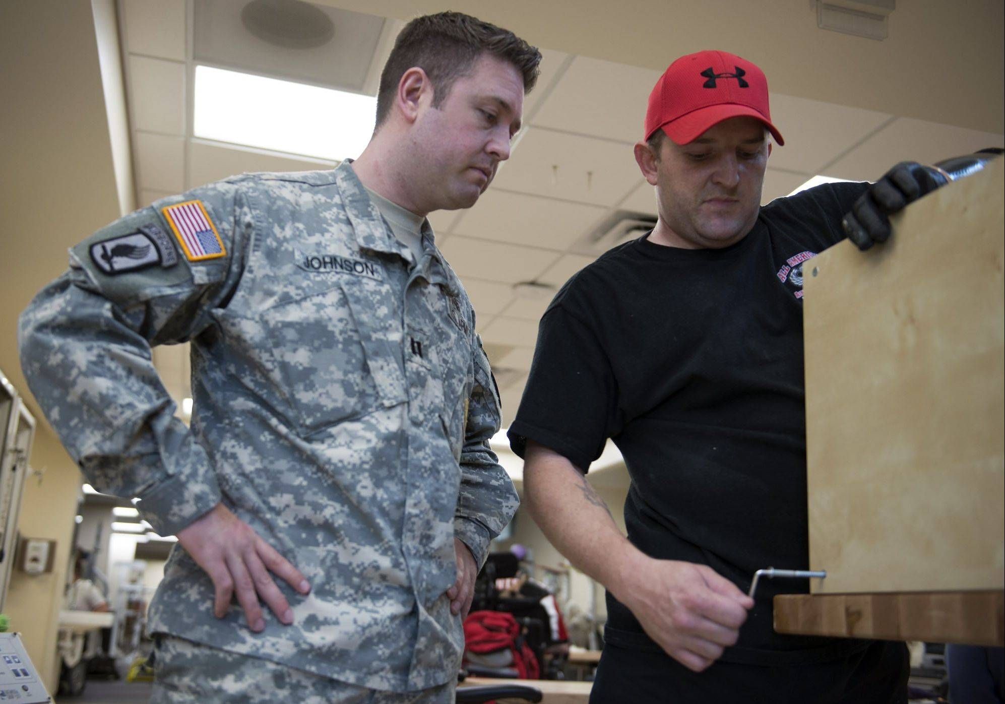 Captain Erik S. Johnson, left, an Army occupational therapist, works with wounded warriors like Army Sargeant Monte Bernardo, helping them achieve some of the things they used to do before receiving their severe injuries.