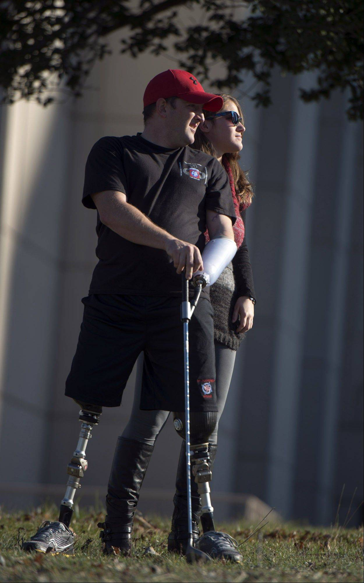 Sergeant Monte Bernardo, left, and his girlfriend Amanda Simmons look to see how far a golf ball traveled across a field at the Walter Reed National Military Medical Center in Bethesda, Md.